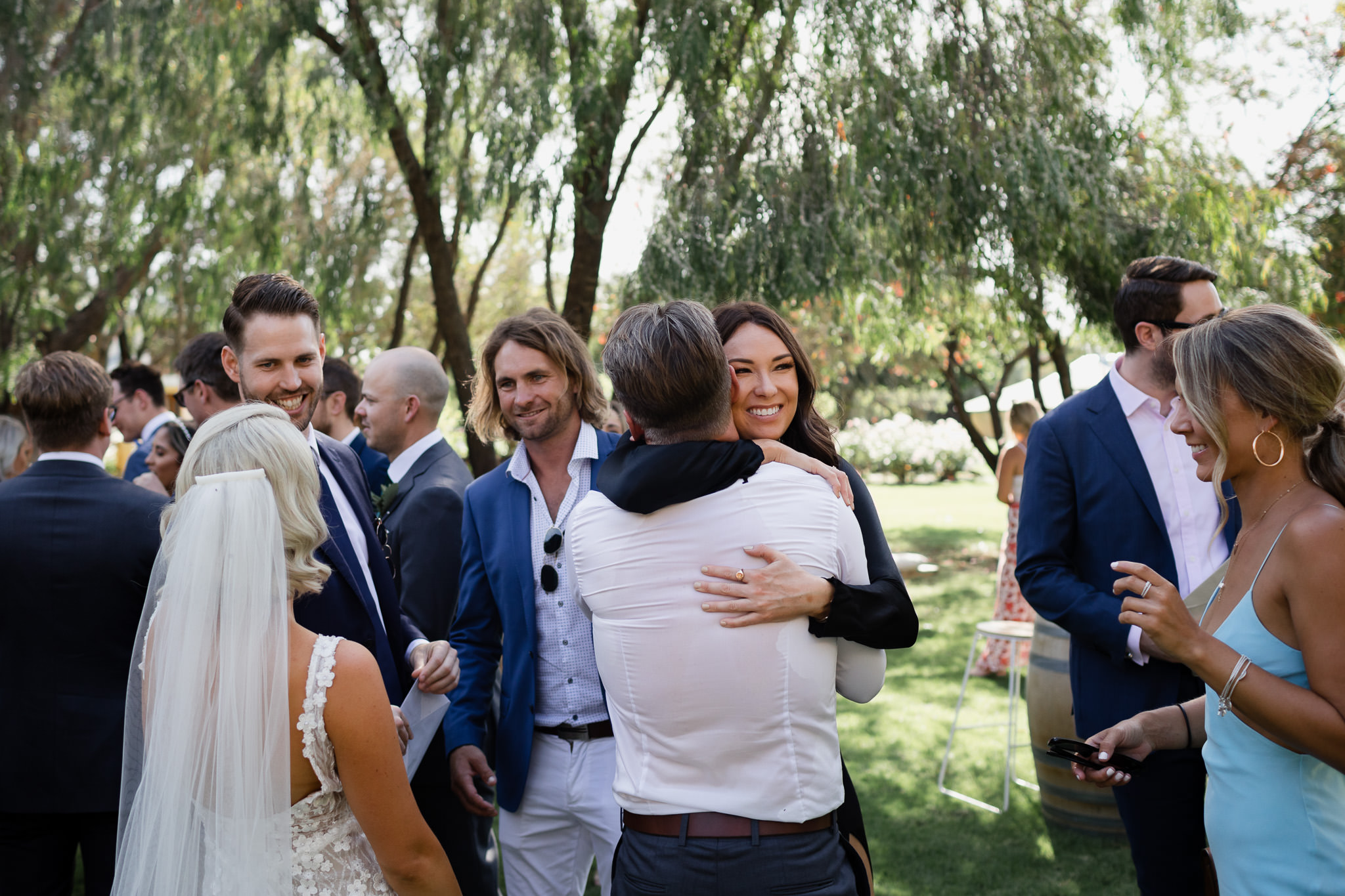 smiling female guest hugging groom after ceremony at an outdoor garden wedding