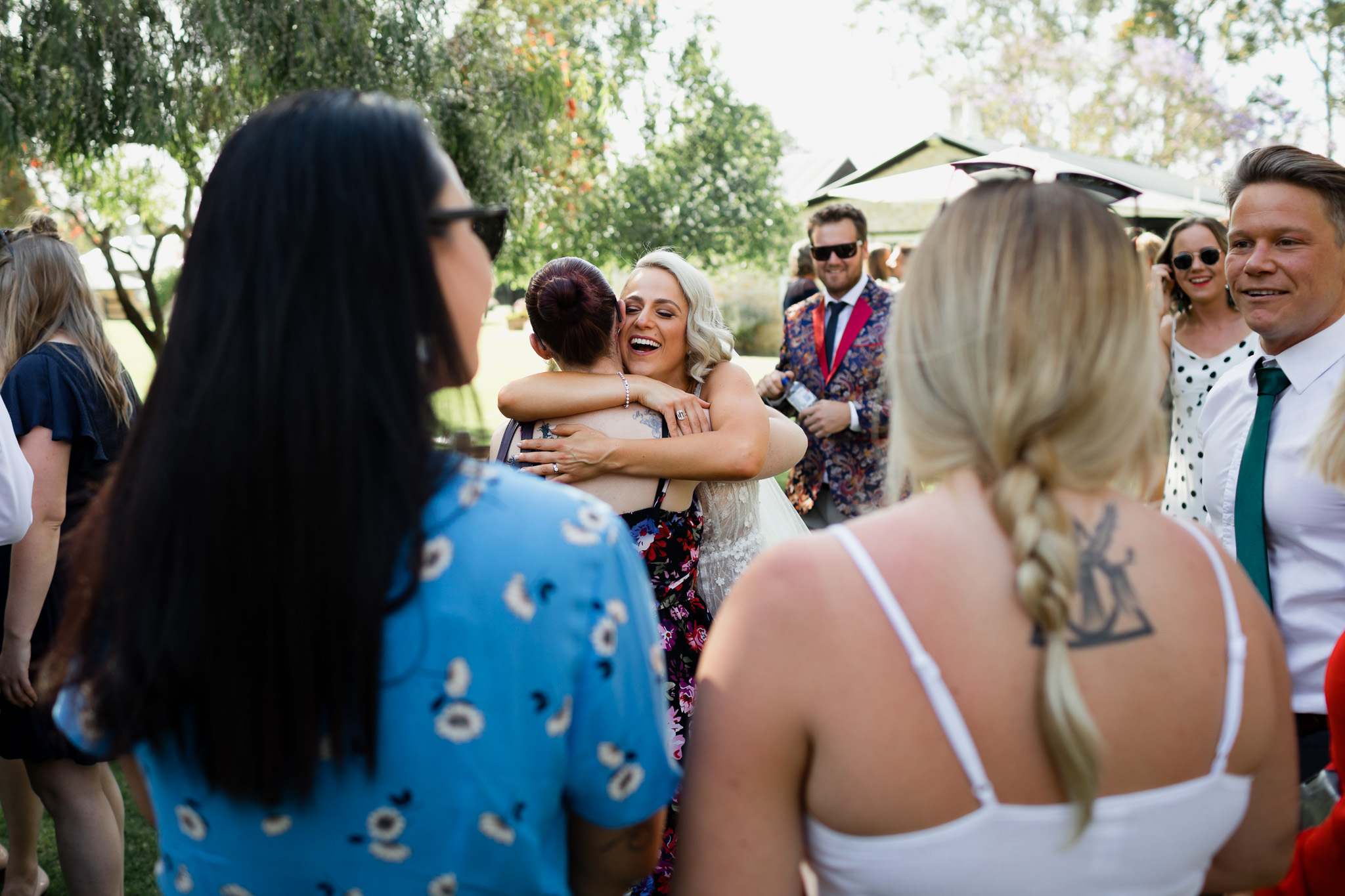 smiling blonde bride hugging friend during congratulations after wedding ceremony, while friends look on
