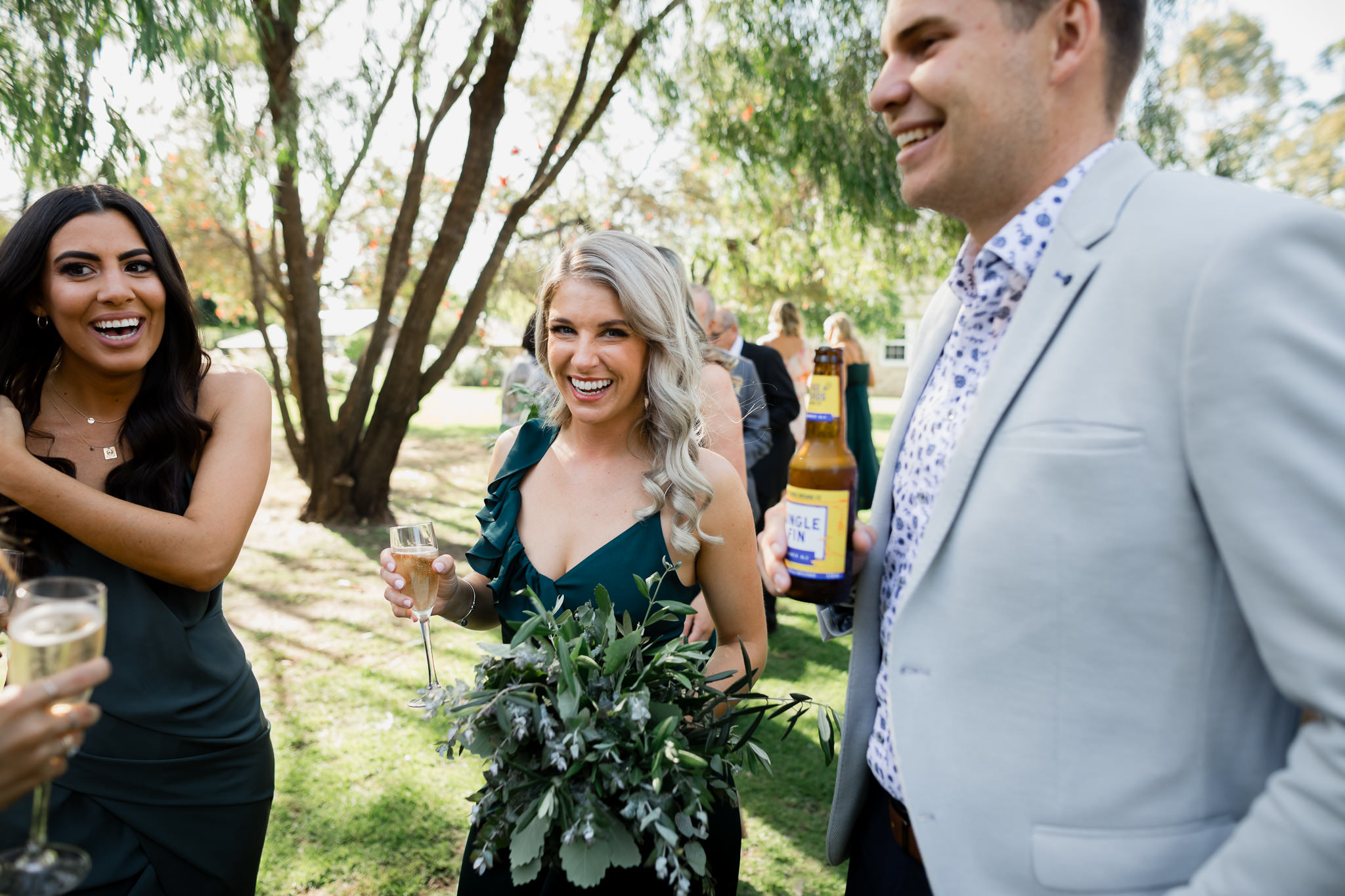blonde bridesmaid in green dress holding champagne and bouquet laughing and smiling with other wedding guests
