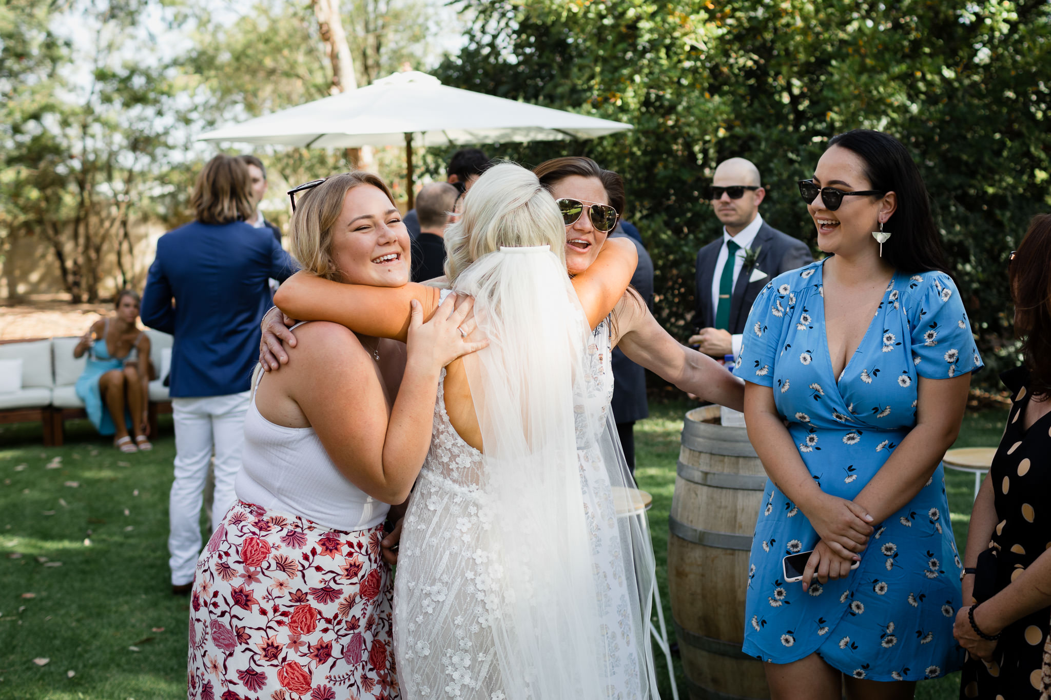 bride hugging two friends at outdoor wedding