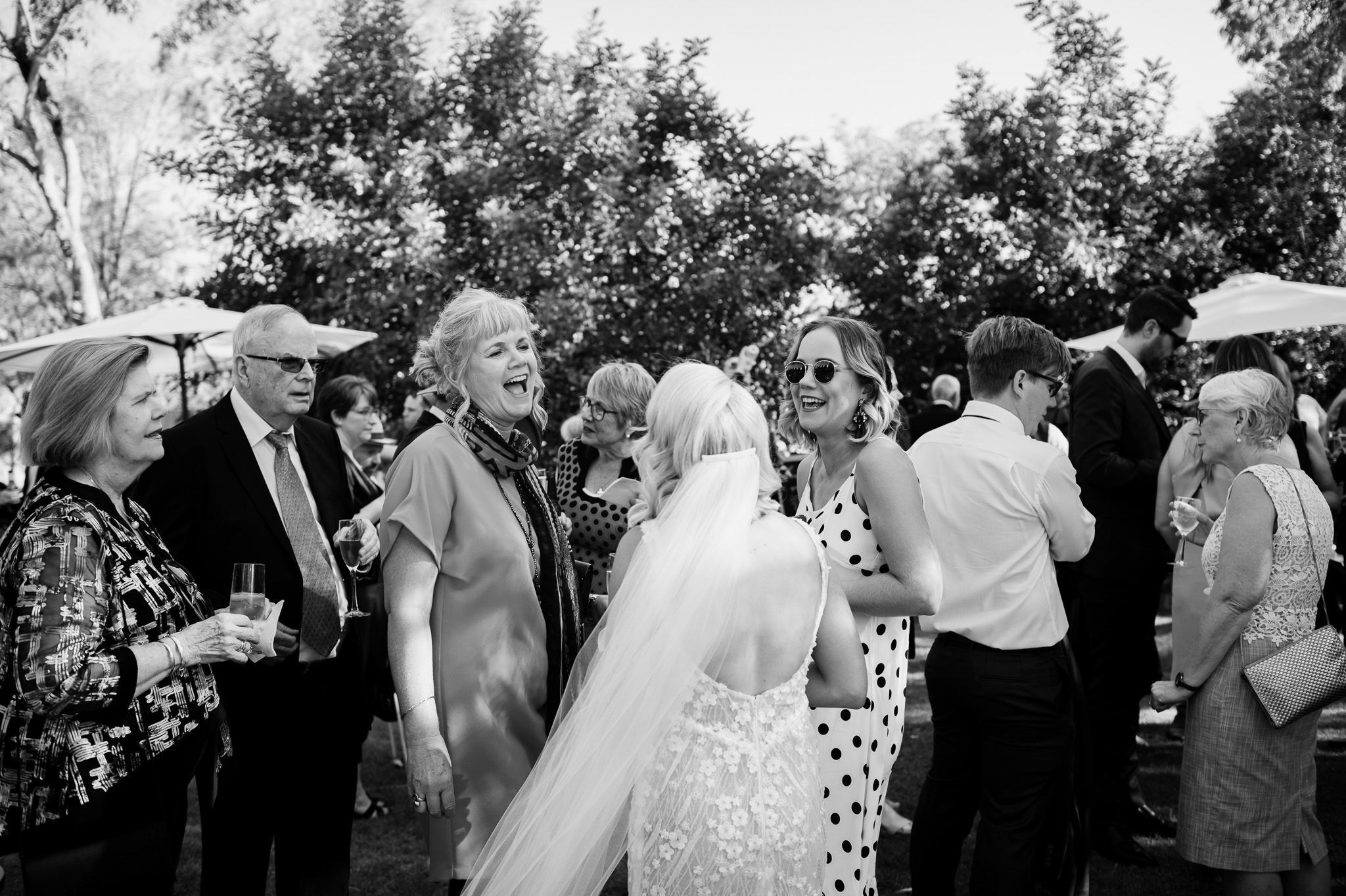 black and white photo of wedding guests laughing with bride