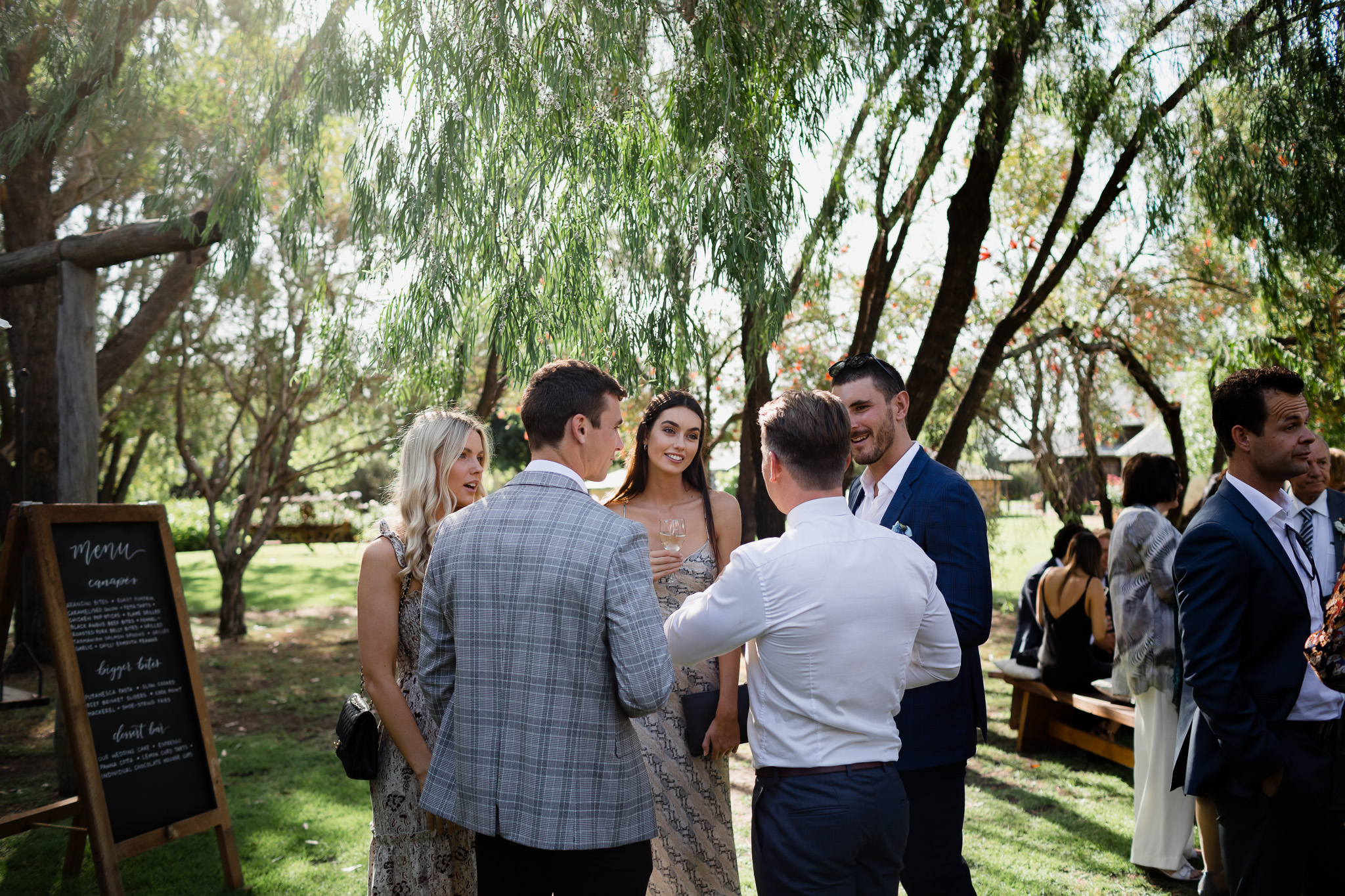 friends chatting and drinking champagne with groom at garden wedding in Busselton Australia