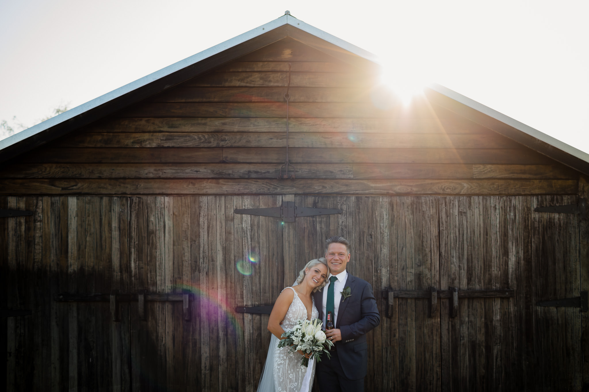 bride and groom smiling at the camera with awesome sun flare striking the historic barn they are standing against
