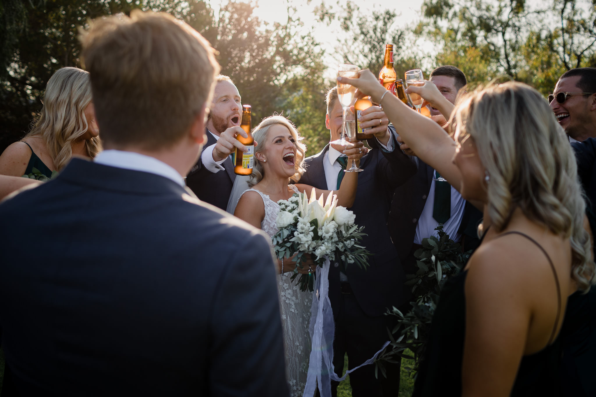 bride and bridal party cheers with champagne and craft beer and white protea bouquet