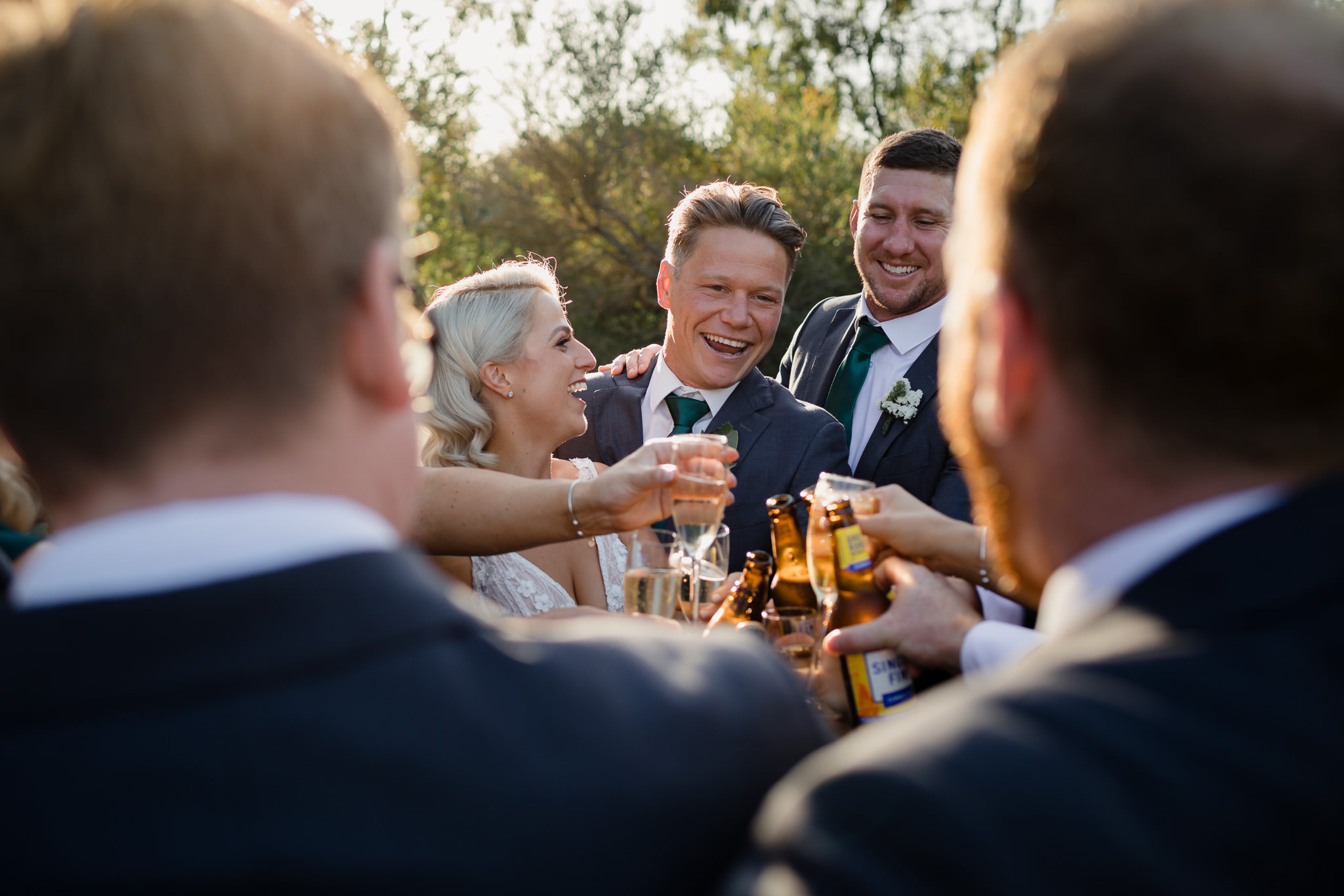 bride and groom clinking beer bottles and champagne glasses with friends