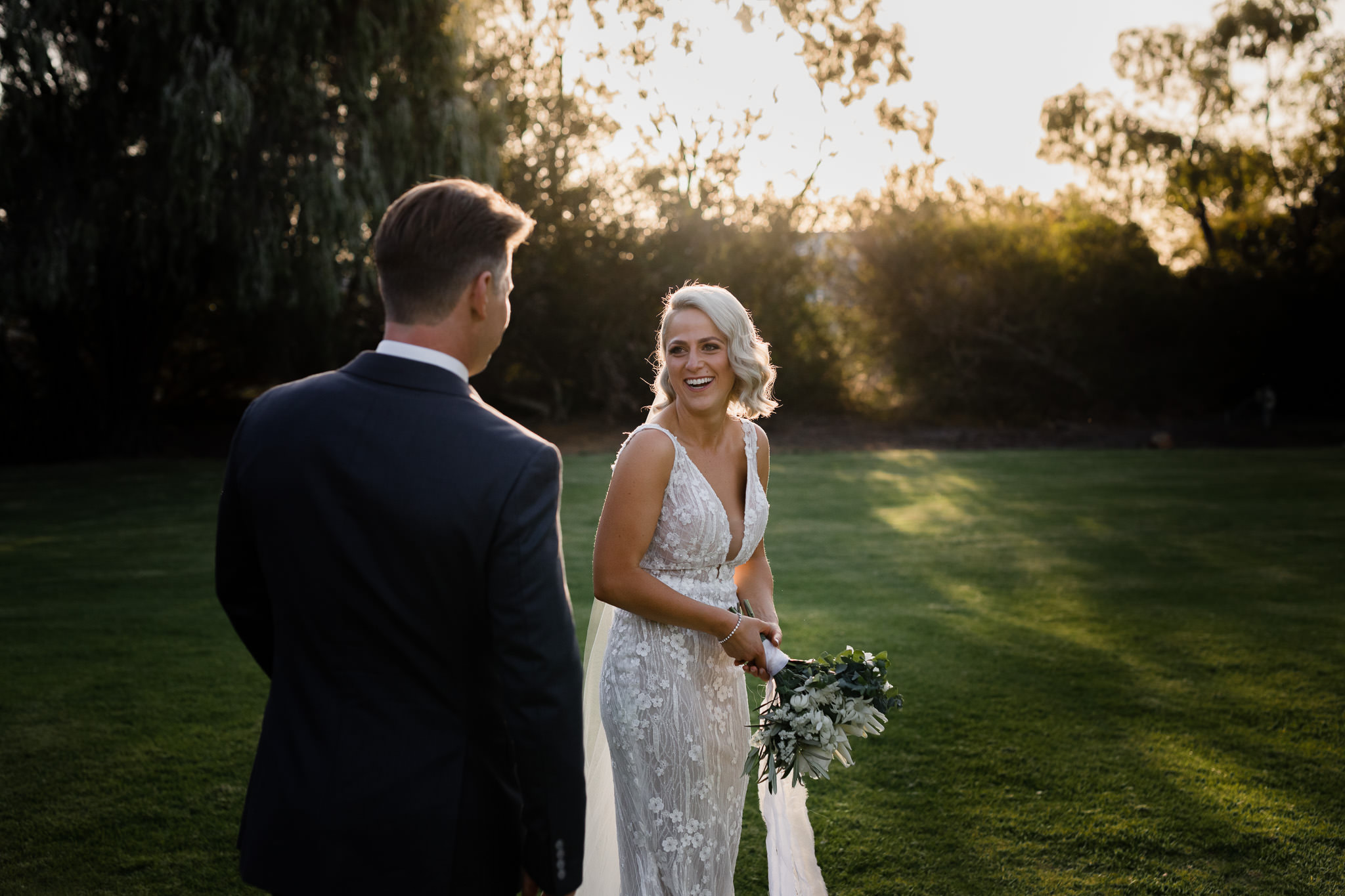 backlit photo of bride in Wedding Societe dress holding native protea bouquet and laughing with her husband with golden light