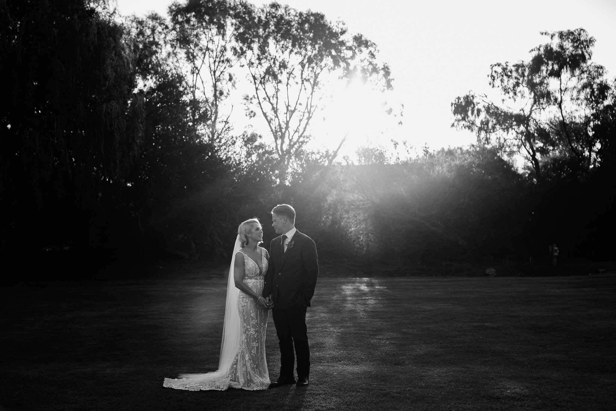 stunning black and white photo of bride and groom looking at each other against dark background at Old Broadwater Farm with glowing sun flare