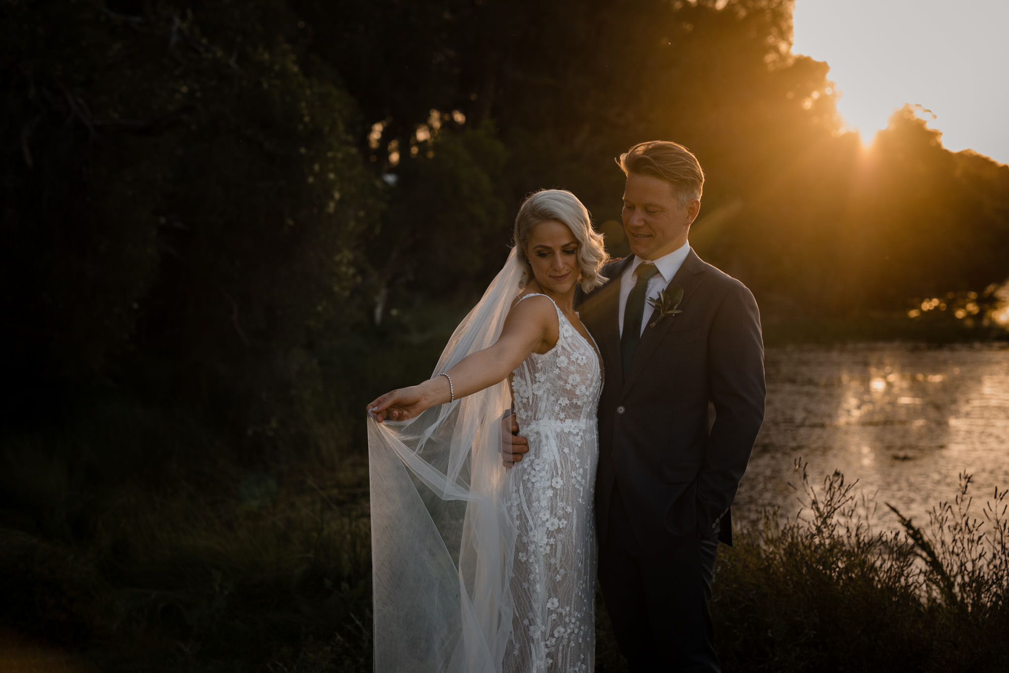 bride playing with veil while groom cuddles her at sunset at Old Broadwater Farm in Busselton