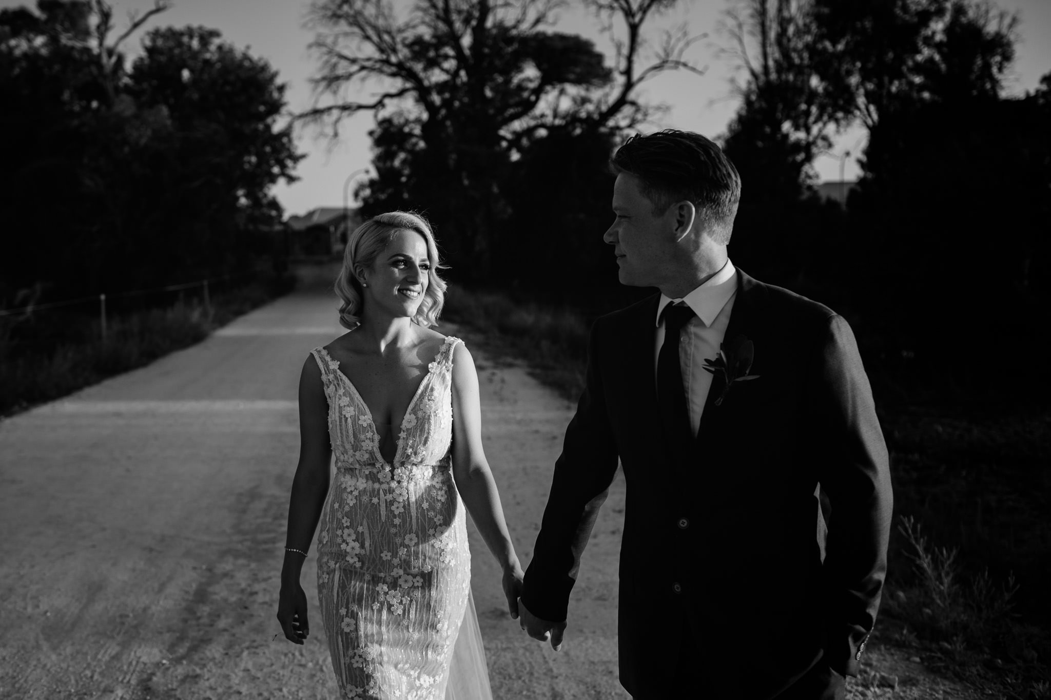 Black and white photo of bride in Wedding Society dress by Aubrey Rose walking with groom at sunset at Old Broadwater Farm