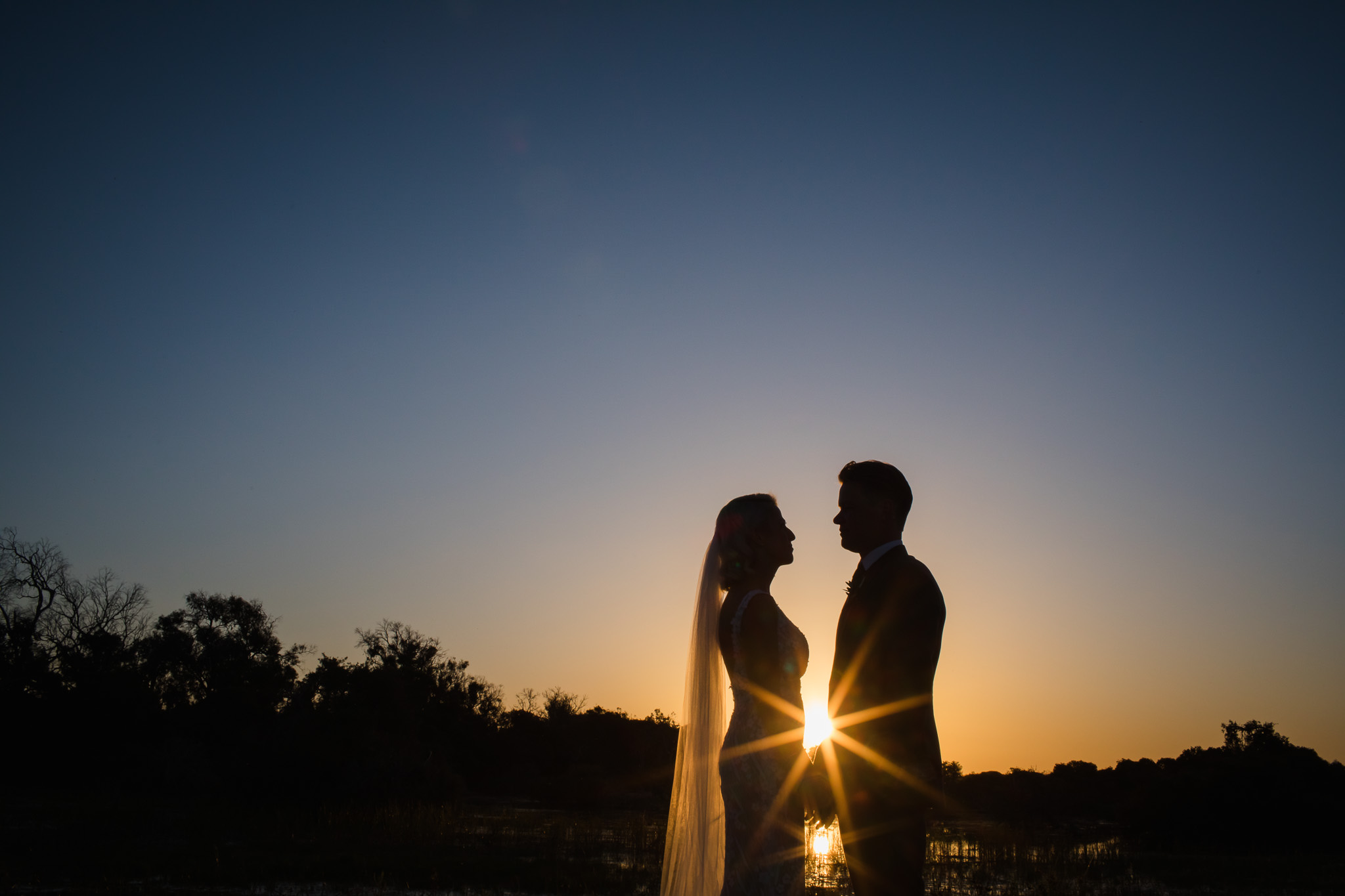 Bride and groom silhouetted at sunset against blue sky with sun star flaring between their bodies