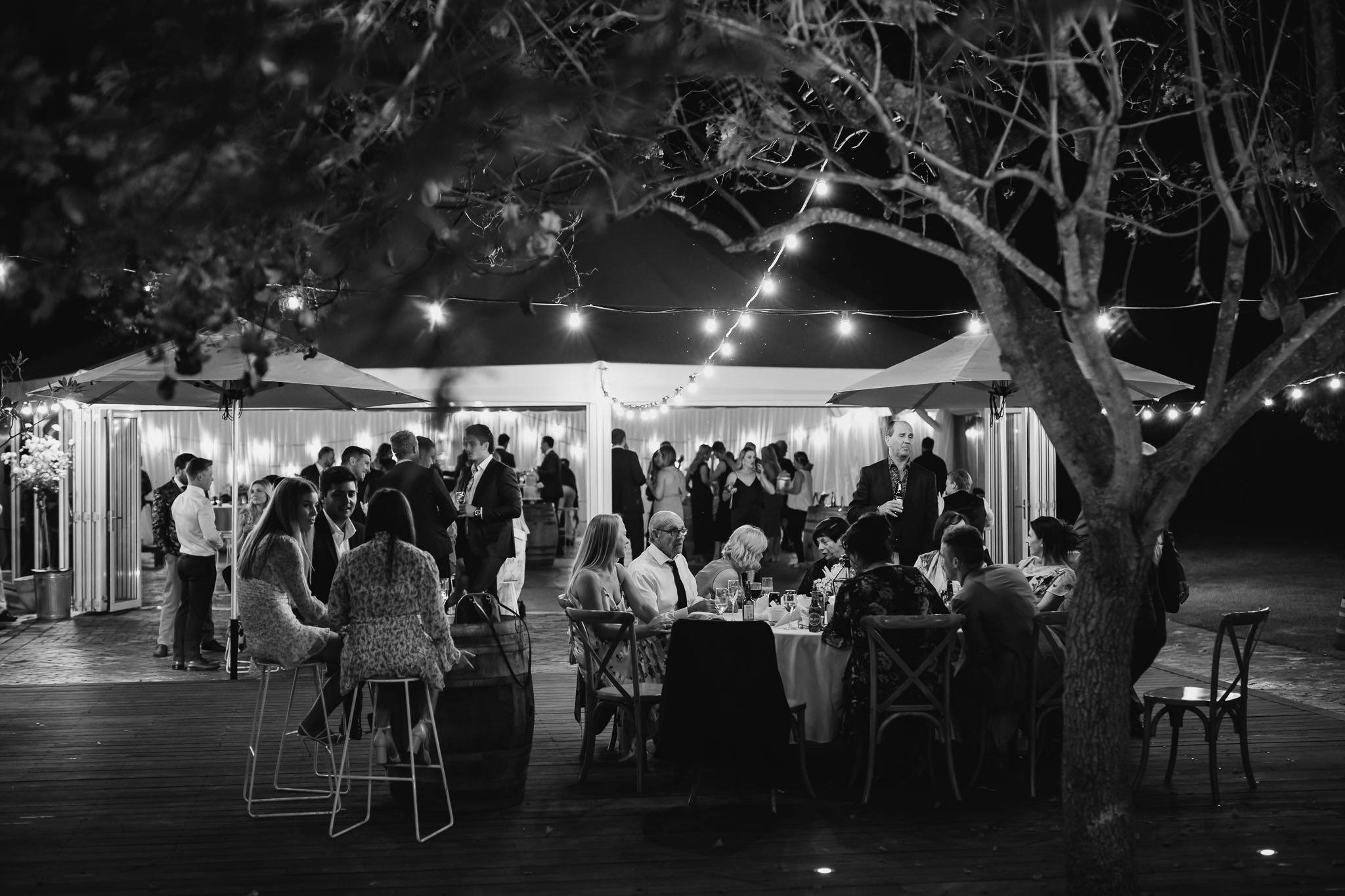 outdoor cocktail reception at night with bar stools and festoon lights under jacaranda trees at Old Broadwater Farm