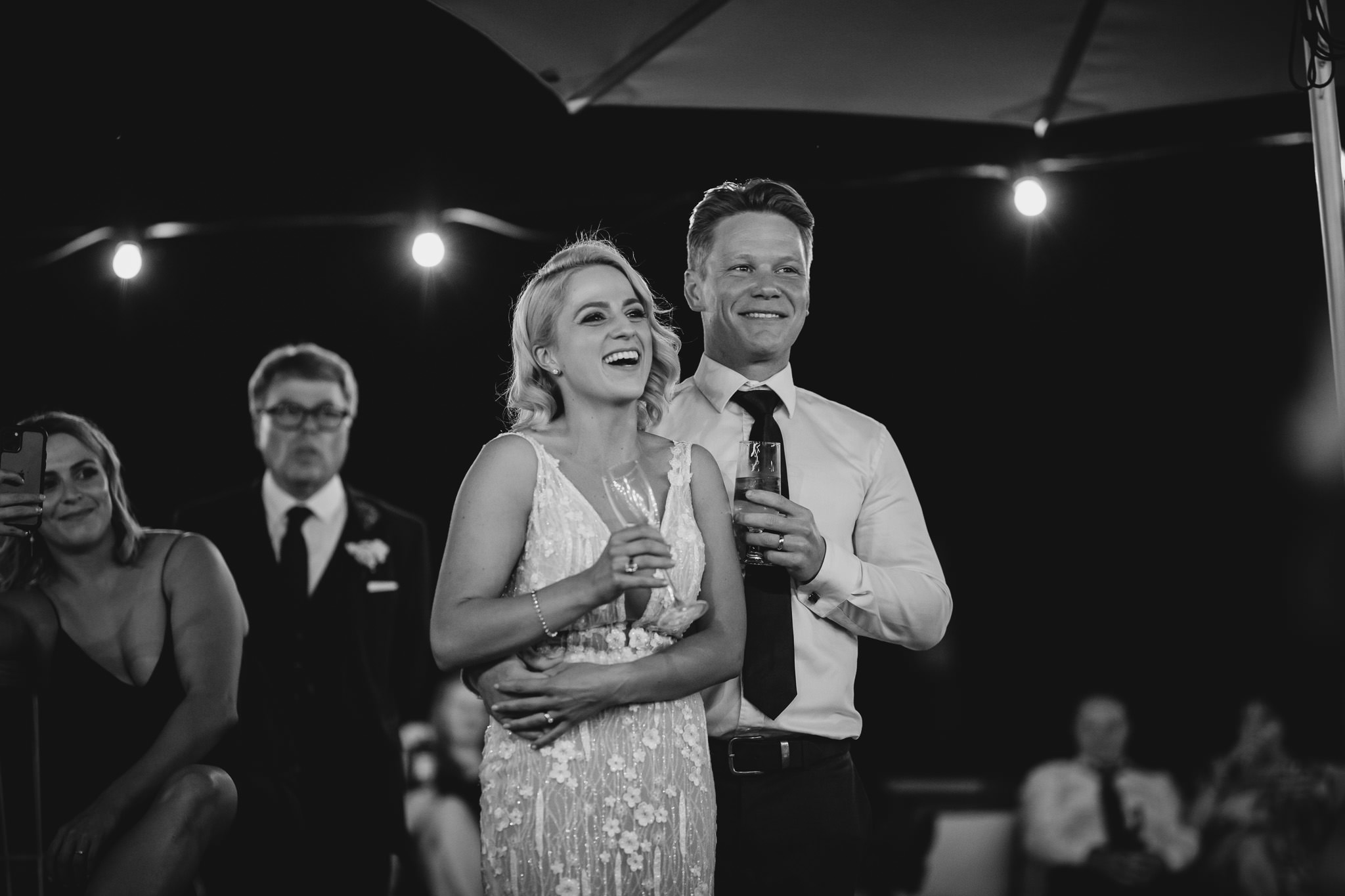 black and white photo of bride and groom laughing during wedding speeches