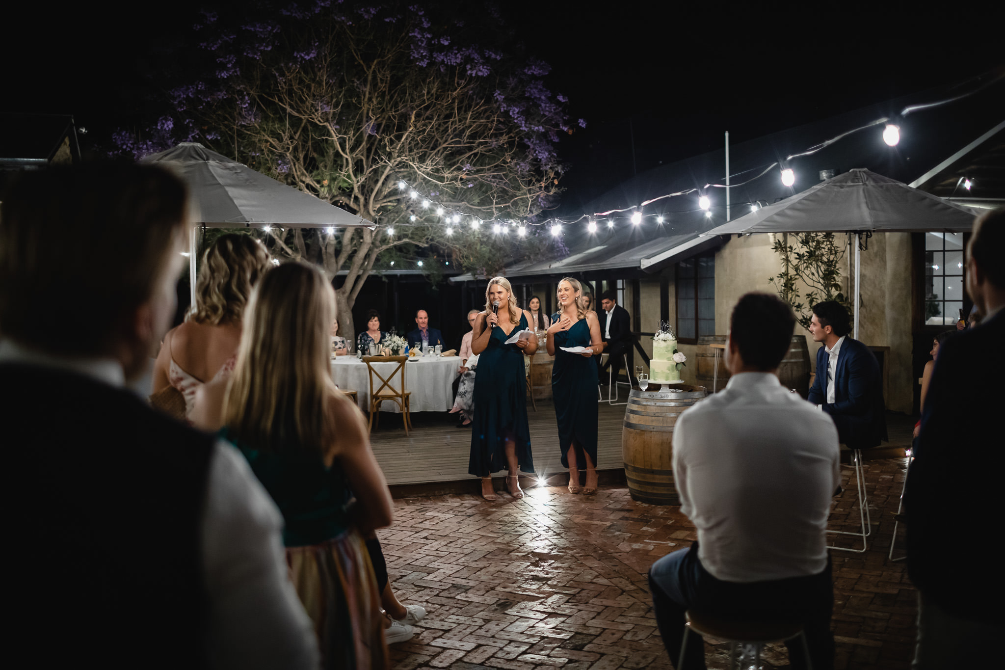 bridesmaids making speech under festoon lights at outdoor cocktail wedding reception