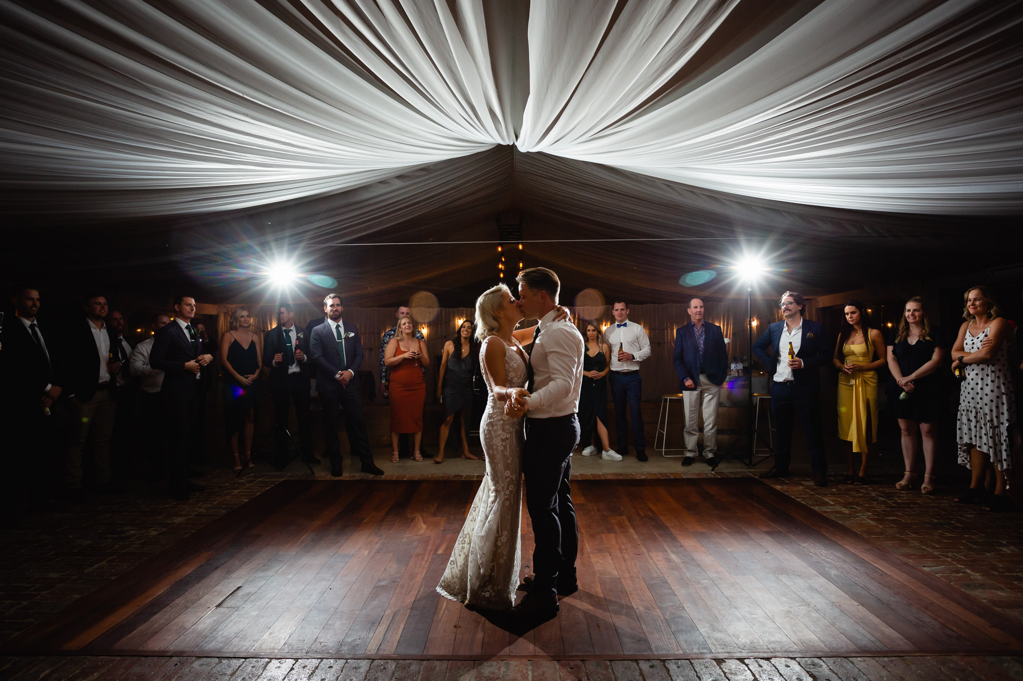 Bride and groom kissing during first dance under white silk ceiling in marquee at Old Broadwater Farm in Busselton