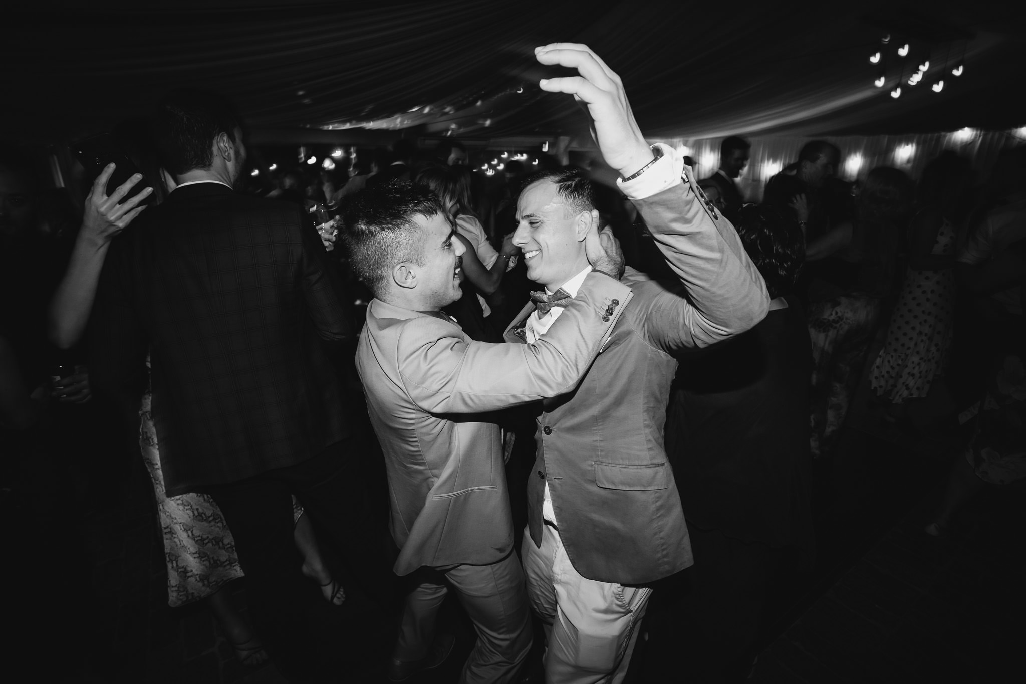 black and white photo of brothers dancing at wedding reception