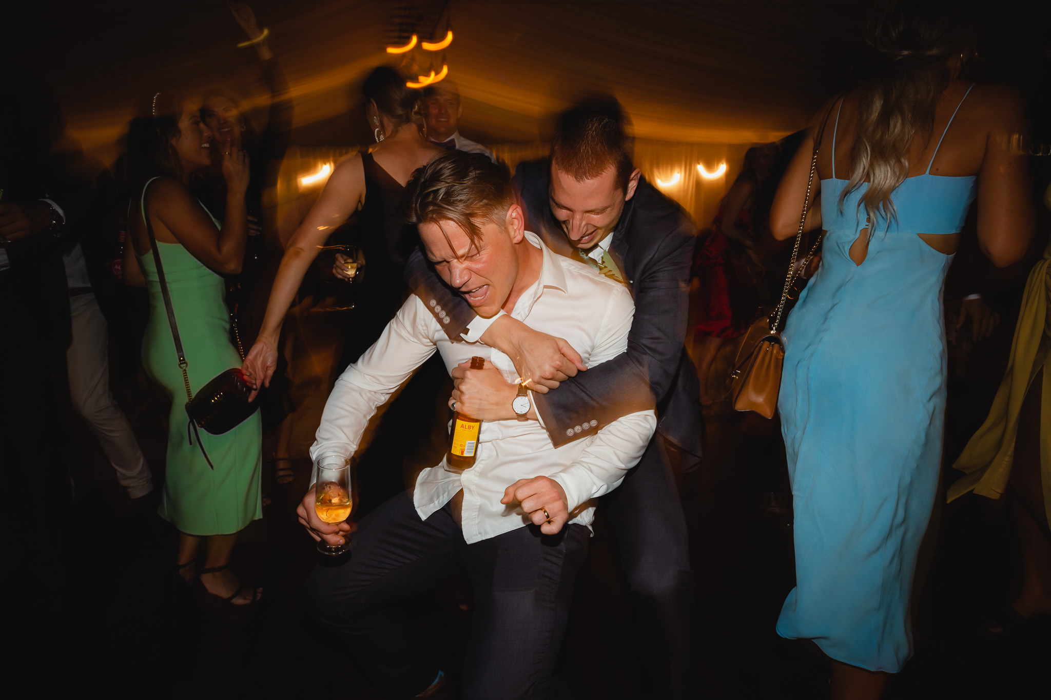 drunken embrace between groom and groomsman on wedding dance floor
