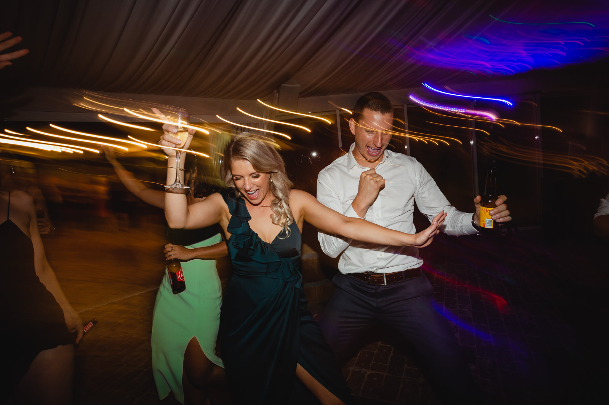 bridesmaid dancing at wedding reception with glass of champagne and light streaks