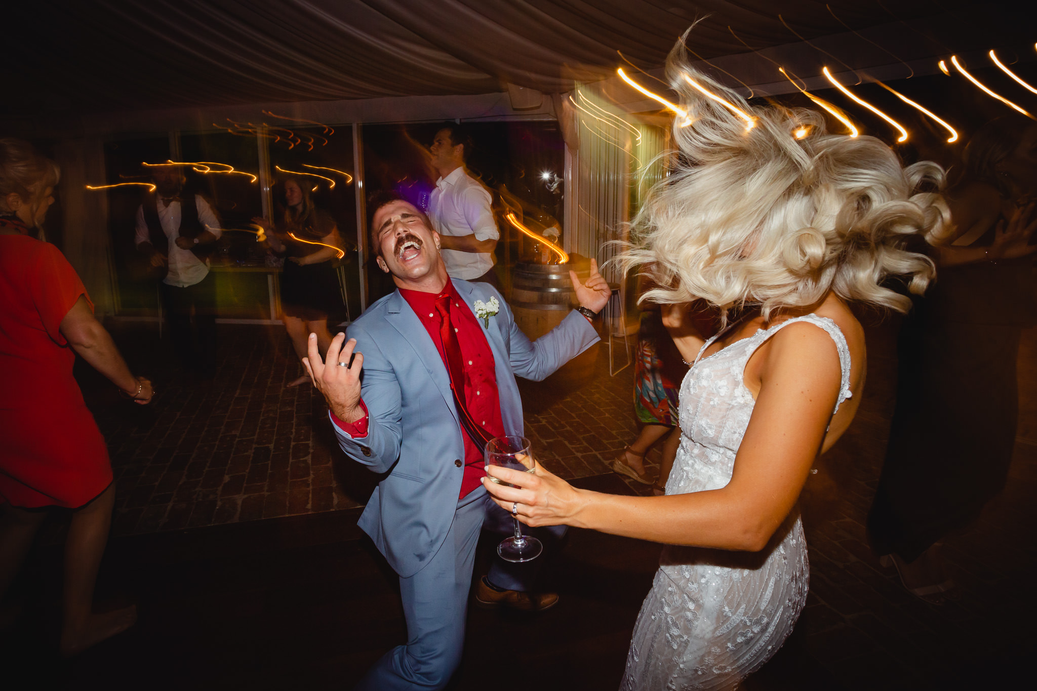party photo of bride shaking hair and dancing with her brother at a wedding