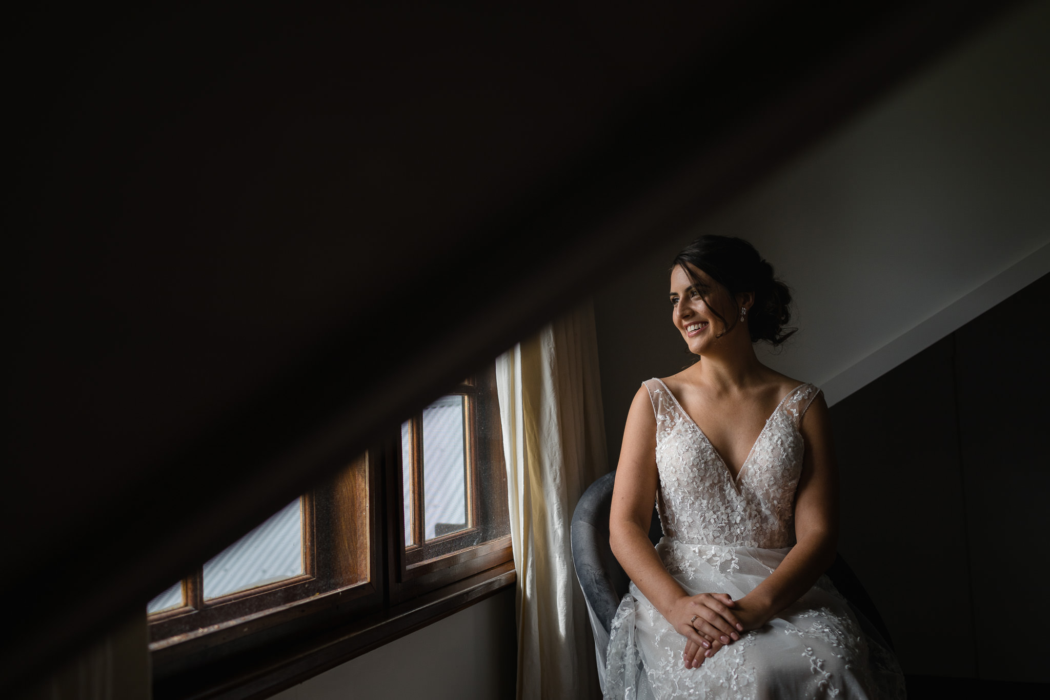 Bride looking out of window in old loft just before her wedding ceremony at Old Broadwater Farm