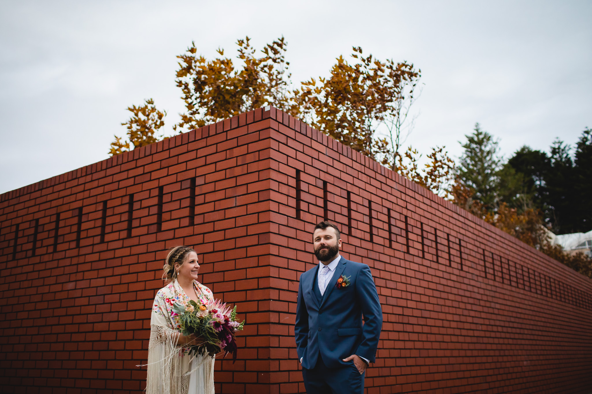Bride with colourful shawl and bouquet and groom posing in front of angular red brick wall in Fremantle after their wedding