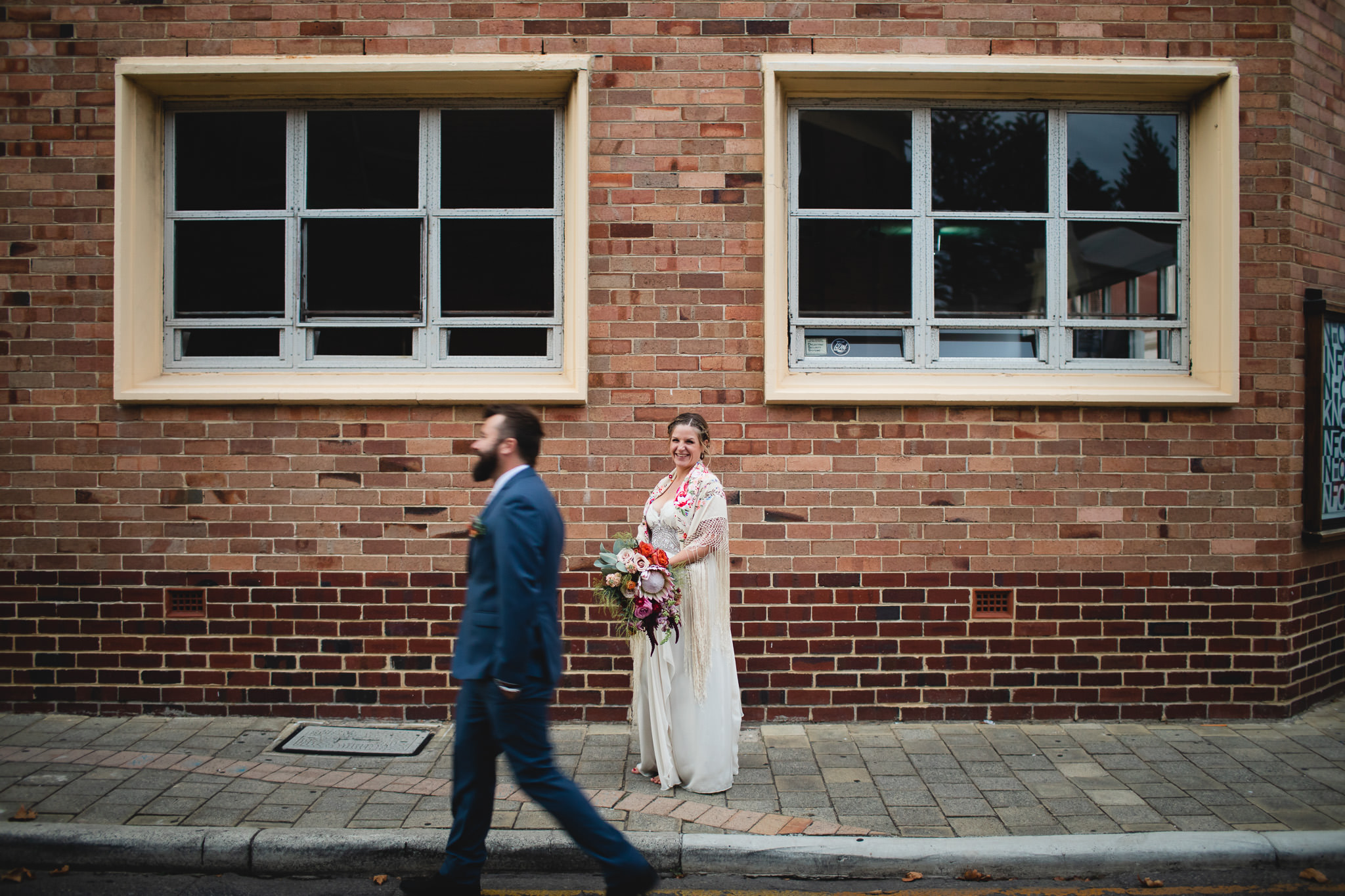 Bride in colourful vintage shawl standing between windows in Fremantle while groom walks past with motion blur