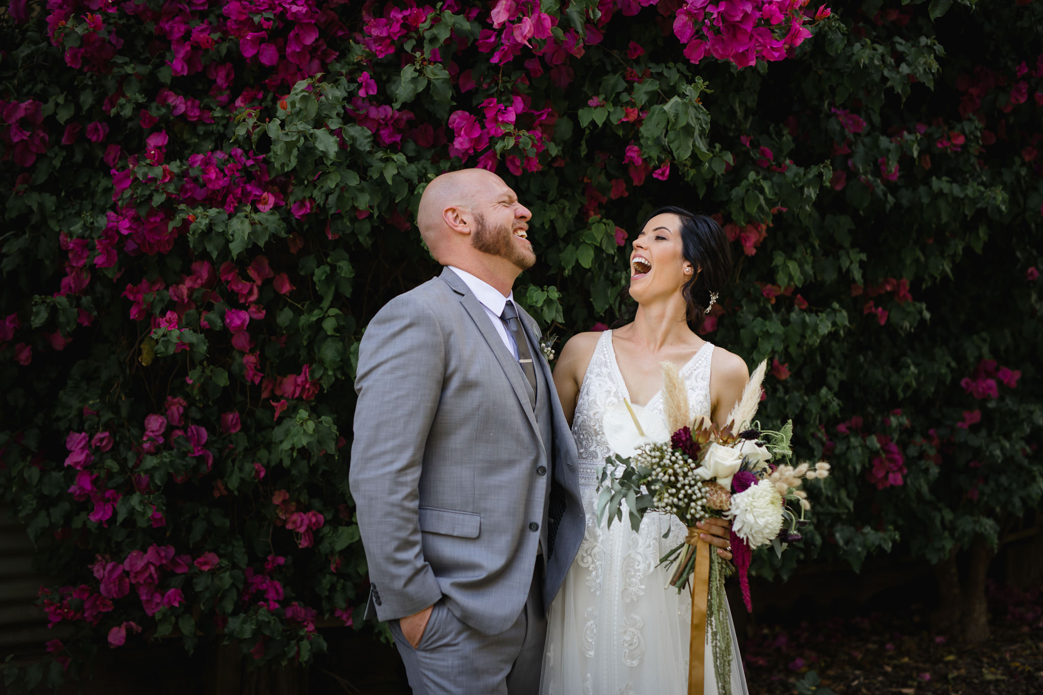 Bride and groom laughing in front of purple Bougainvillea flowers at their wedding at Leeuwin Estate in Margaret River