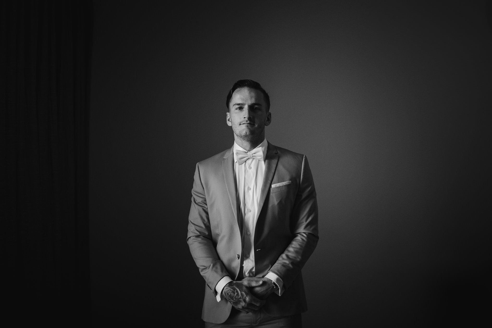 Black and white photo of tattooed groom with bow tie in dark room on his wedding day