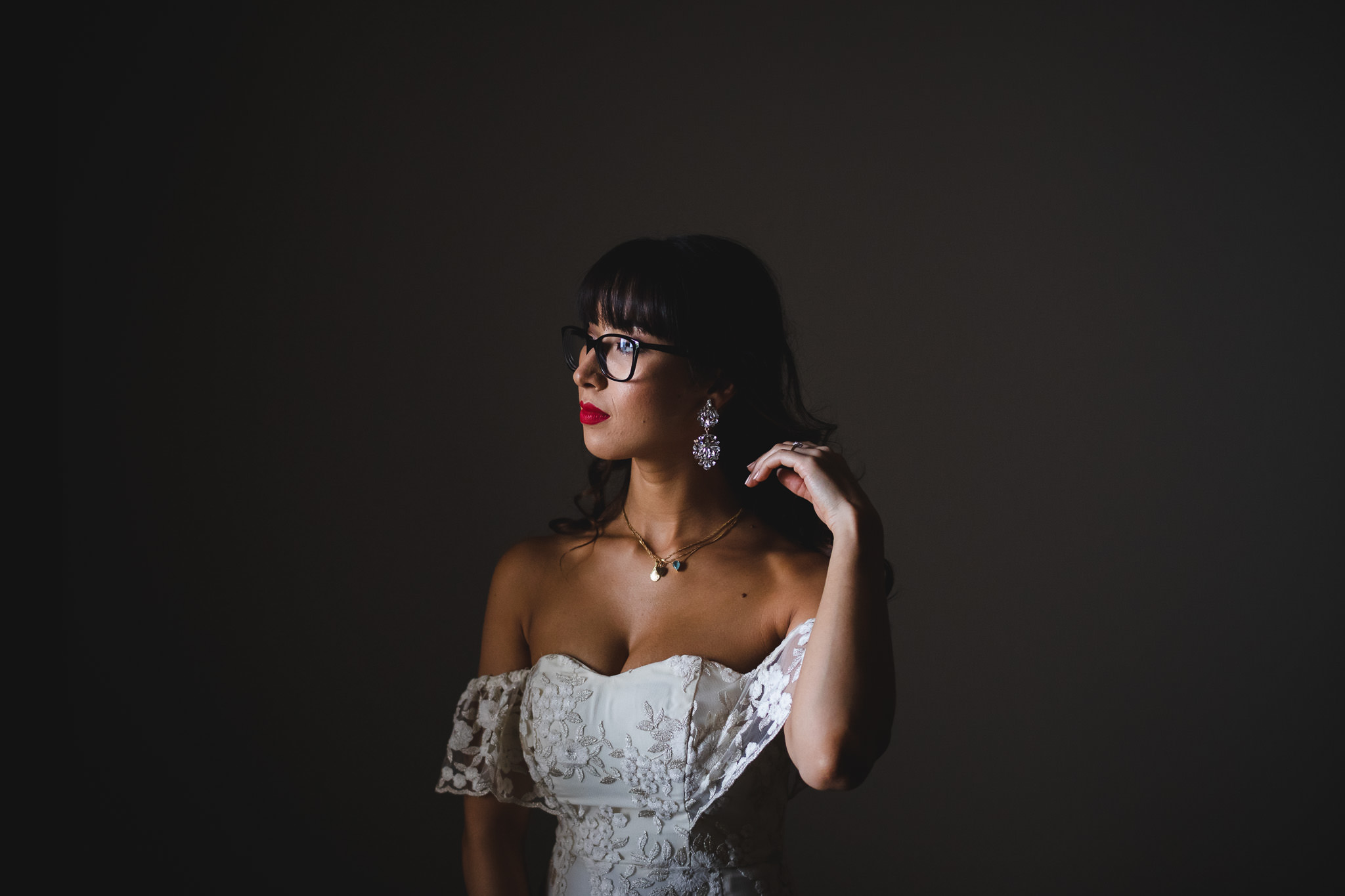 Brazilian bride with glasses and red lipstick sweeping her hair in dark room with soft window light