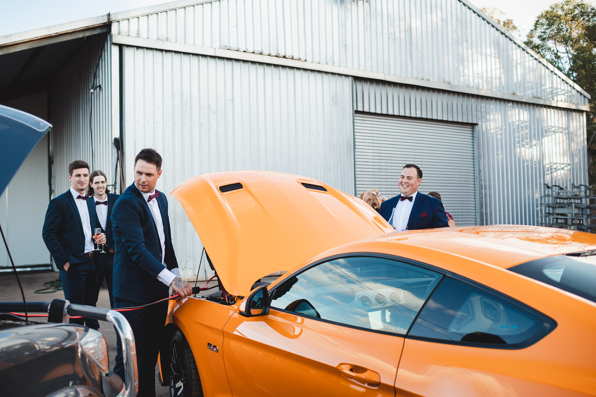 Groom and groomsmen jumping starting yellow Mustang after the car battery went flat during the wedding ceremony at Happs Wines
