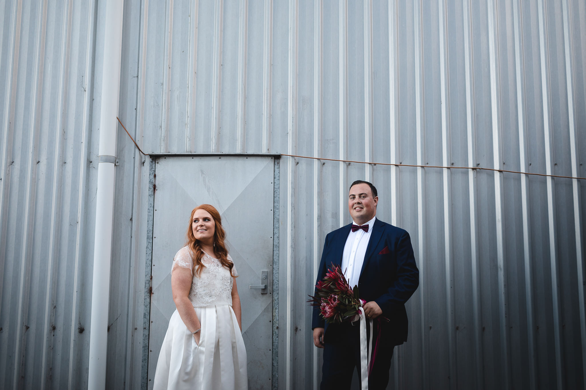 Vintage style bride with orange hair and groom holding bouquet while standing in front of industrial sheds at Happs Wines