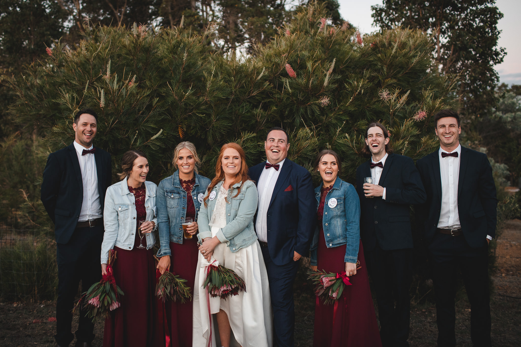 bride and bridesmaids in denim jackets laughing with groomsmen in front of grevillea bushes at backyard wedding in Yallingup
