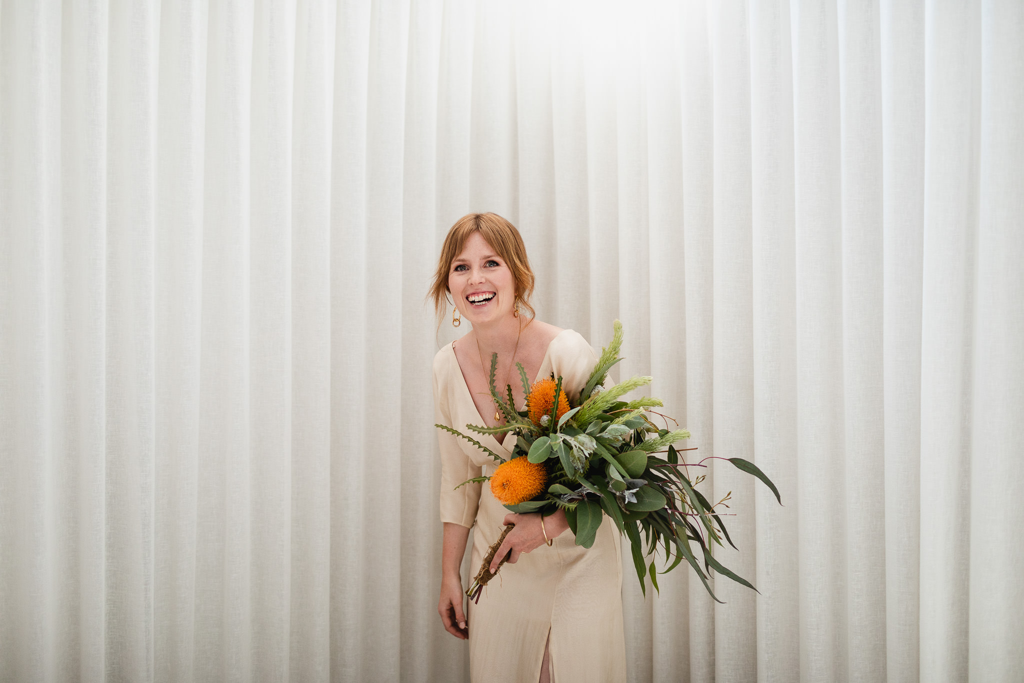 Bride with red hair laughing while holding a wedding bouquet with orange and yellow banksia and native Australian flowers