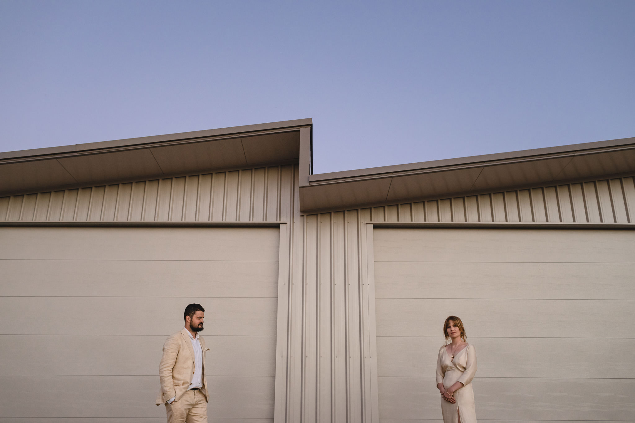 bride and groom standing apart from each other in front of zig zag roofline of double garage at their backyard wedding in Yallingup