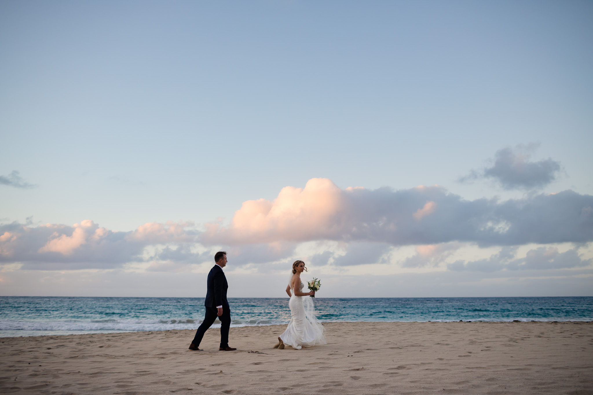 Wedding photo of bride and groom walking along Bunker Bay Beach at their autumn wedding with pink clouds behind them