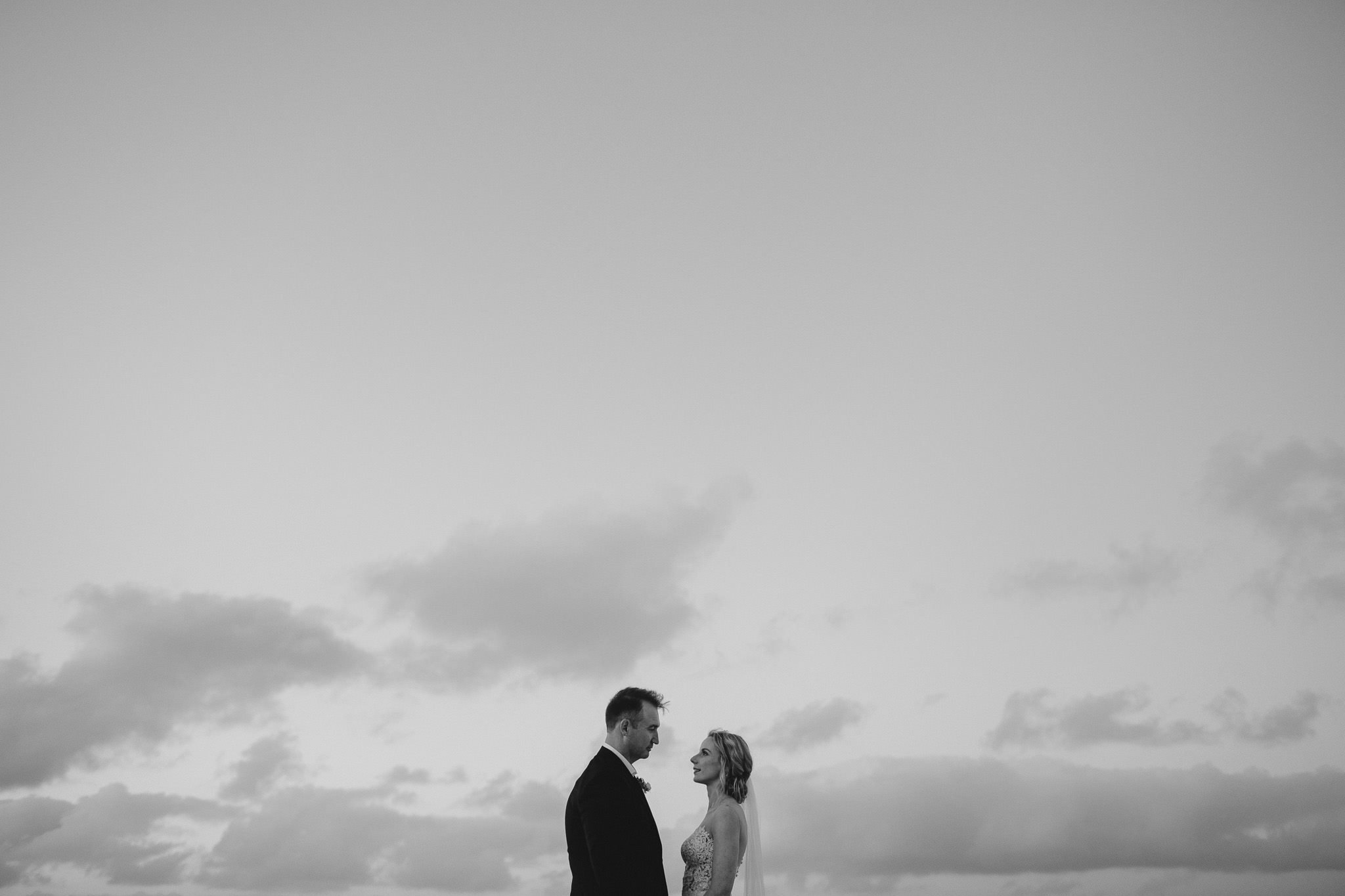 Bride and groom looking at each other with plenty of negative space and cloudy sky behind them at their autumn wedding at Bunker Bay Beach