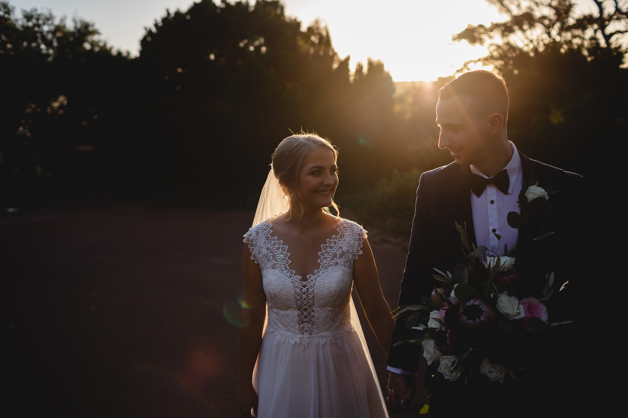 wedding photo of bride and groom walking in front of dark scene while sun flare creates a halo around them at Pearl River Houses in Margaret River