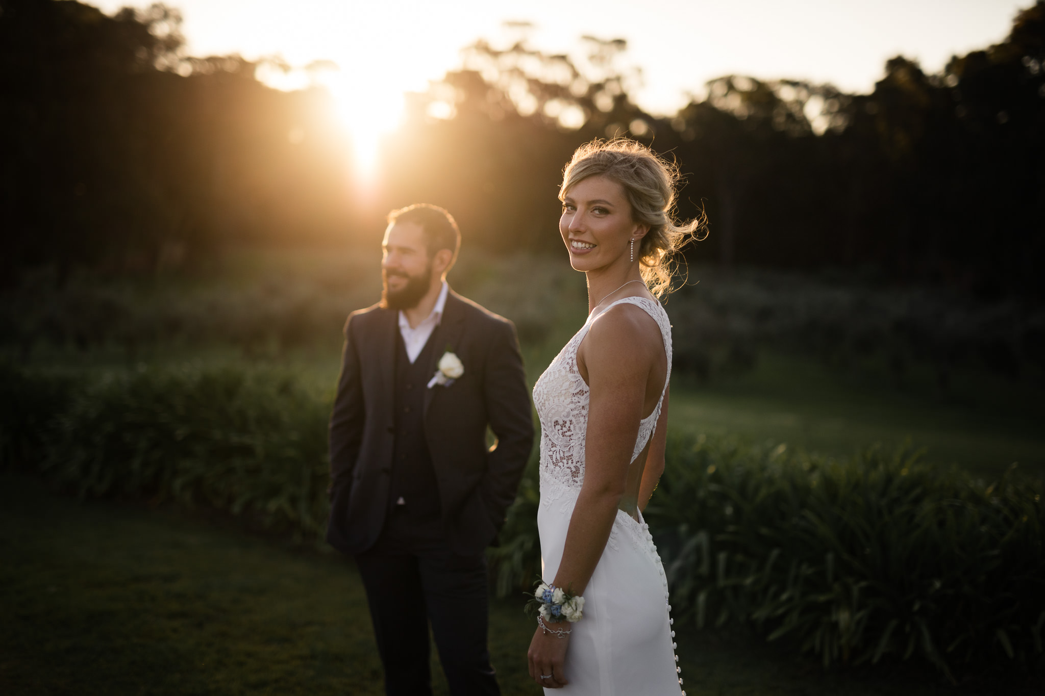 Bride looking over her shoulder at sunset with glowing light at Robert Oatley in Margaret River on her wedding day
