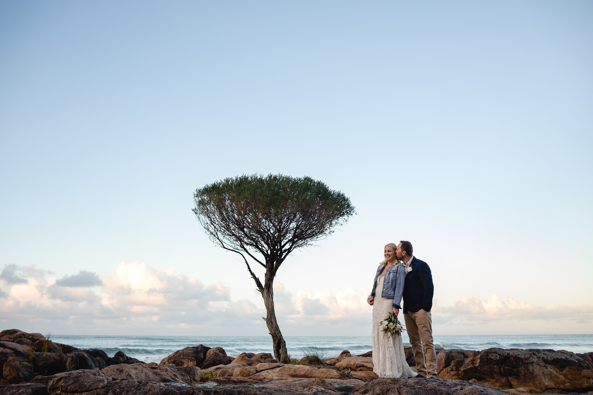 bride in denim jacket leaning back into groom with lone tree at the beach in Dunsborough at their wedding