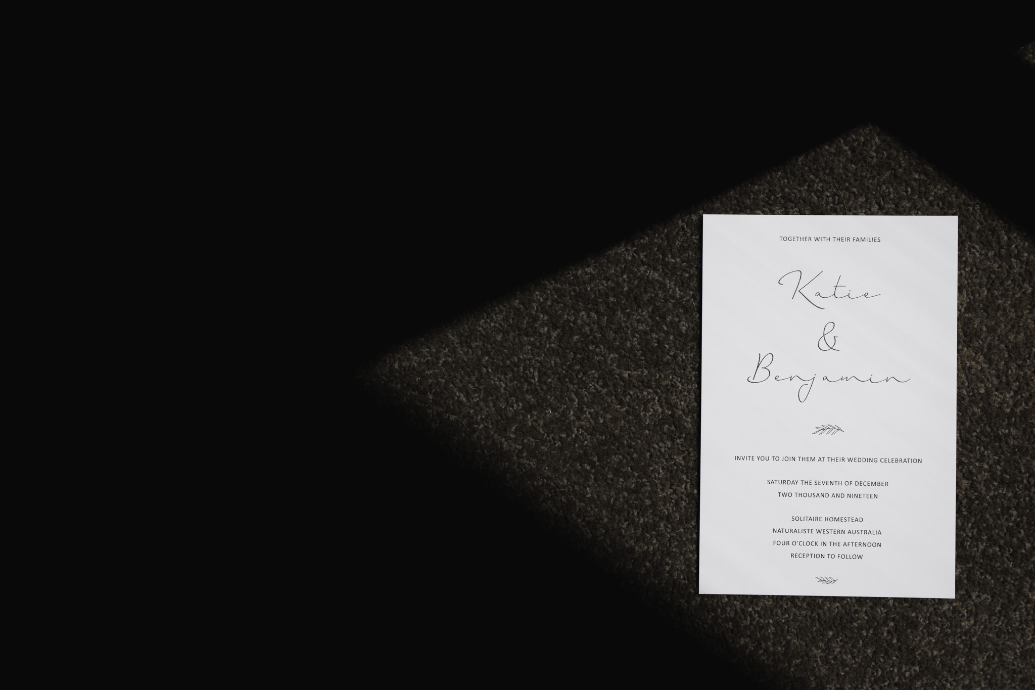 Black and white photo of modern wedding letterpress invitation in shadows