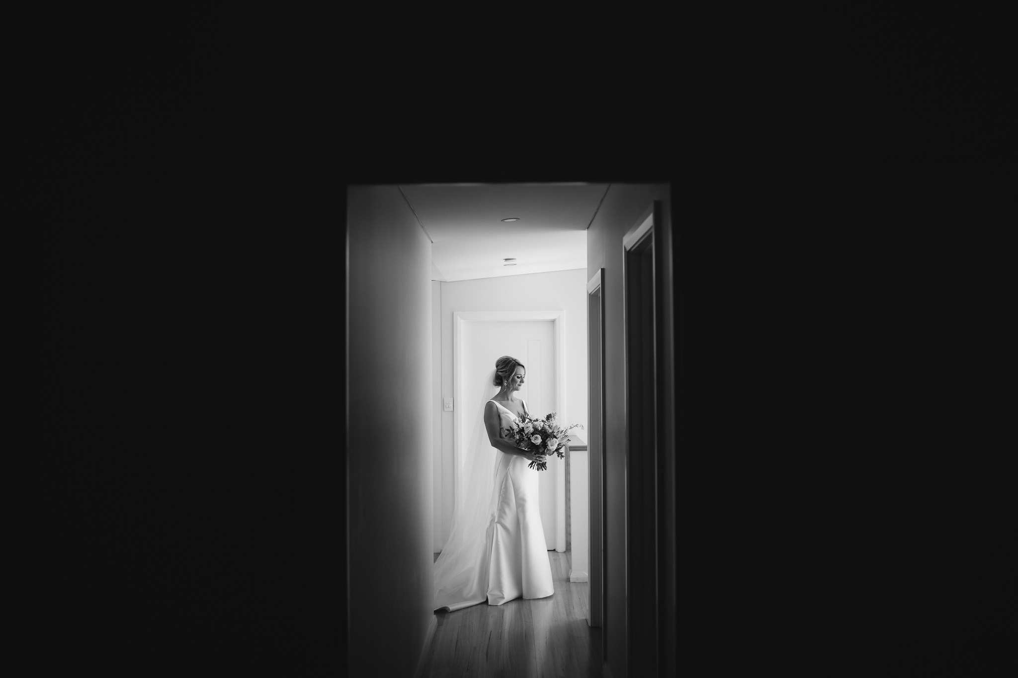 Black and white portrait of bride in hallway before her wedding ceremony