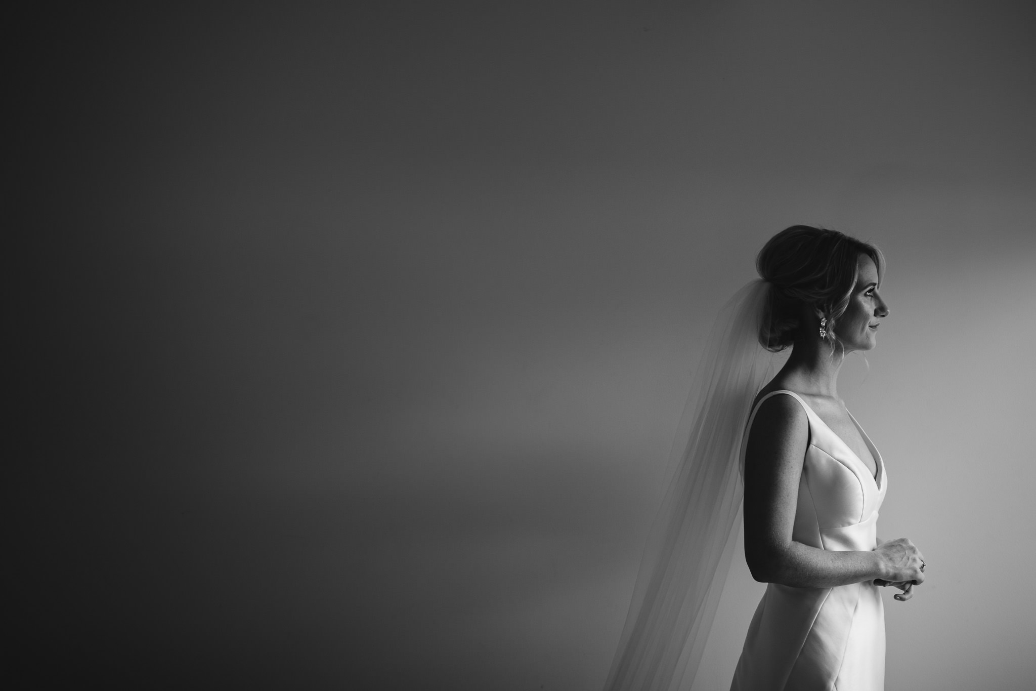 Black and white photo of bride in dark room looking out of window with negative space behind her