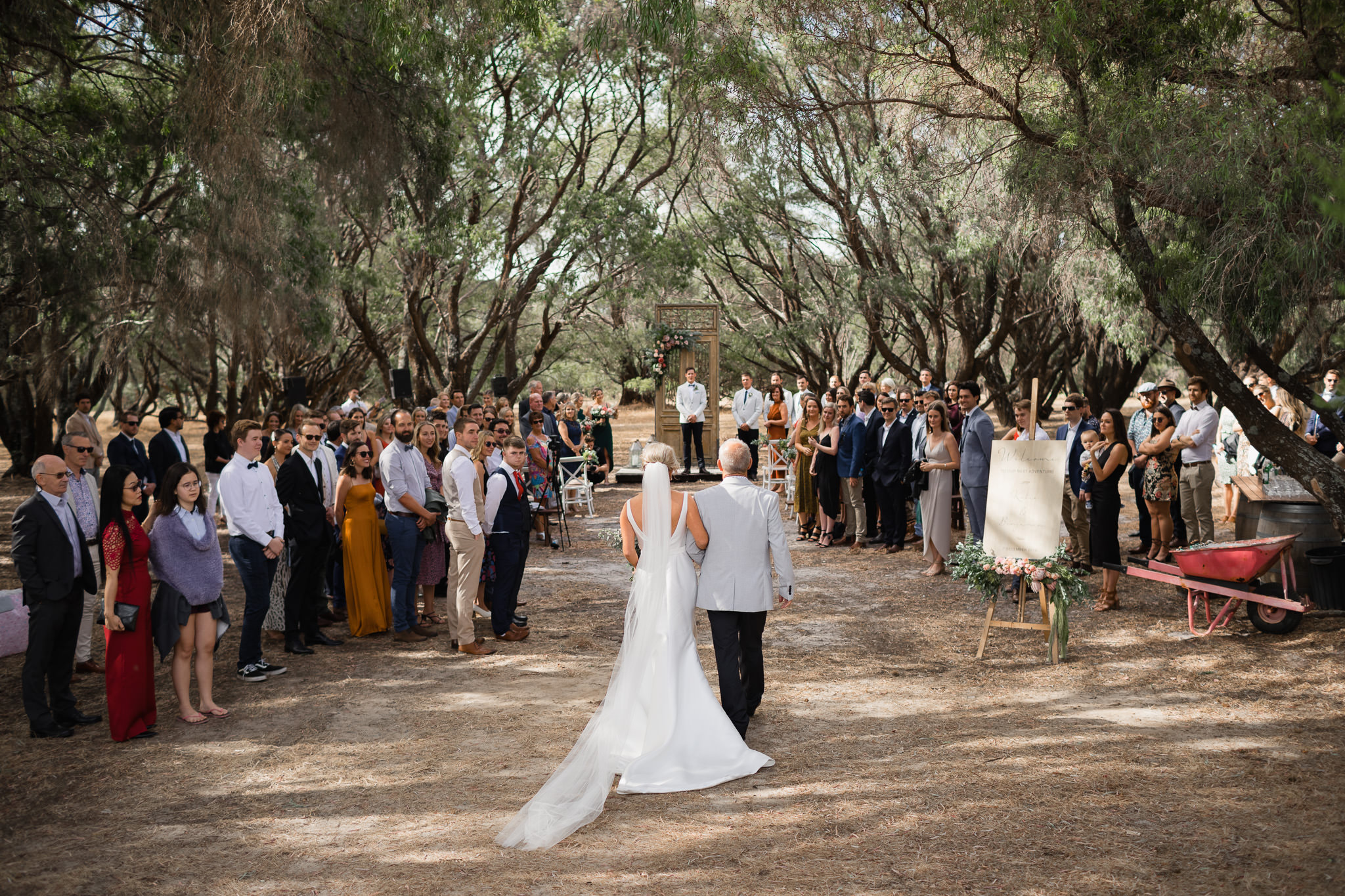 Bride and father walking down aisle at wedding in peppermint trees at Solitaire Homestead while groom and wedding guests look on