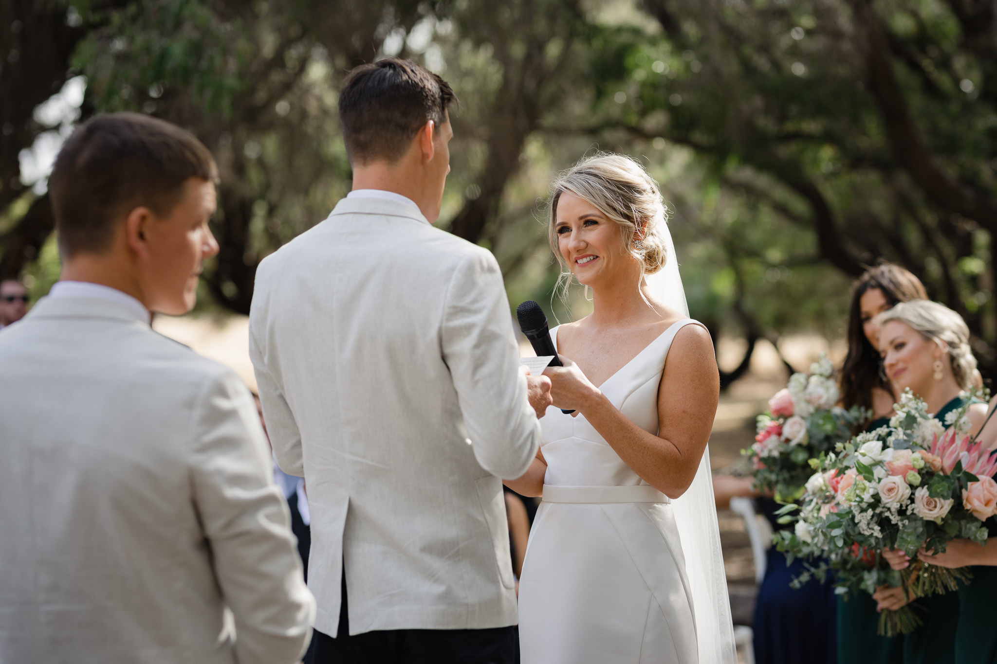 Bride holding microphone towards groom at ceremony while he delivers personalised wedding vows