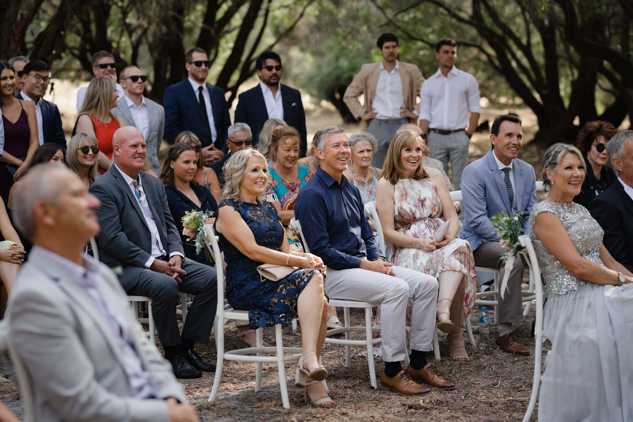Happy wedding guests laughing during outdoor ceremony in Yallingup