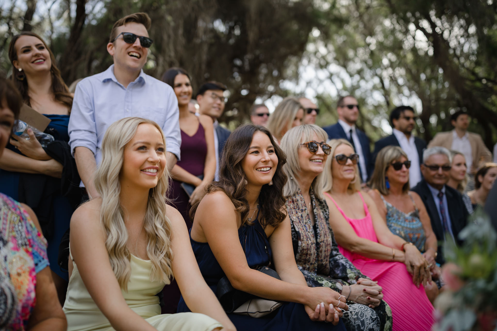 Smiling wedding guests watching ceremony at a bush wedding in Yallingup, Western Australia