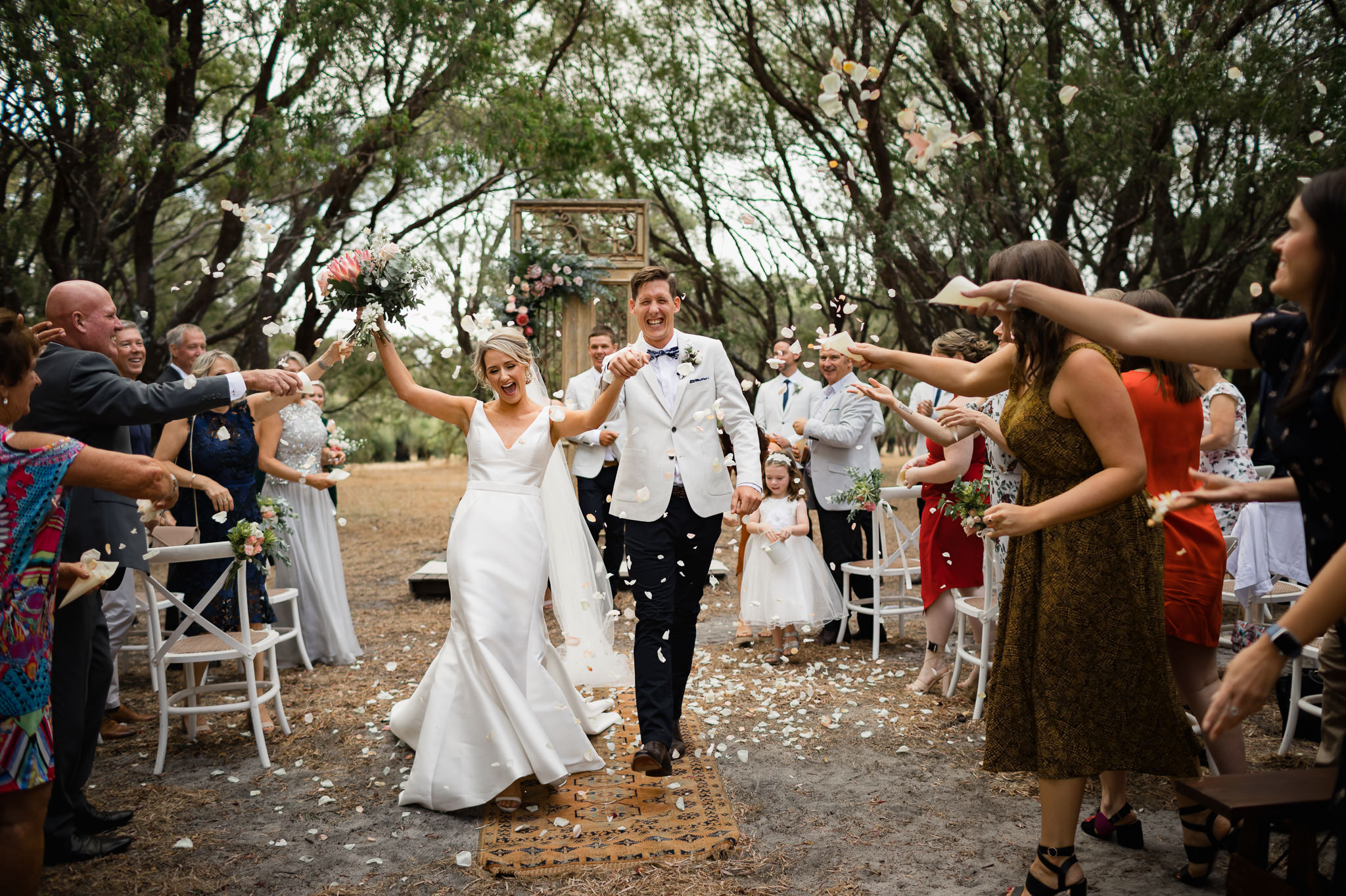 Bride and groom walking back down aisle after wedding as guests throw white petals and confetti over them at Solitaire Homestead in Yallingup
