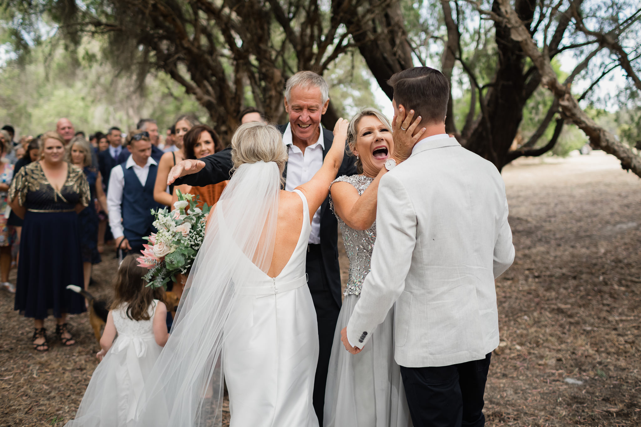Mother of the groom excitedly hugging son after wedding ceremony in Yallingup