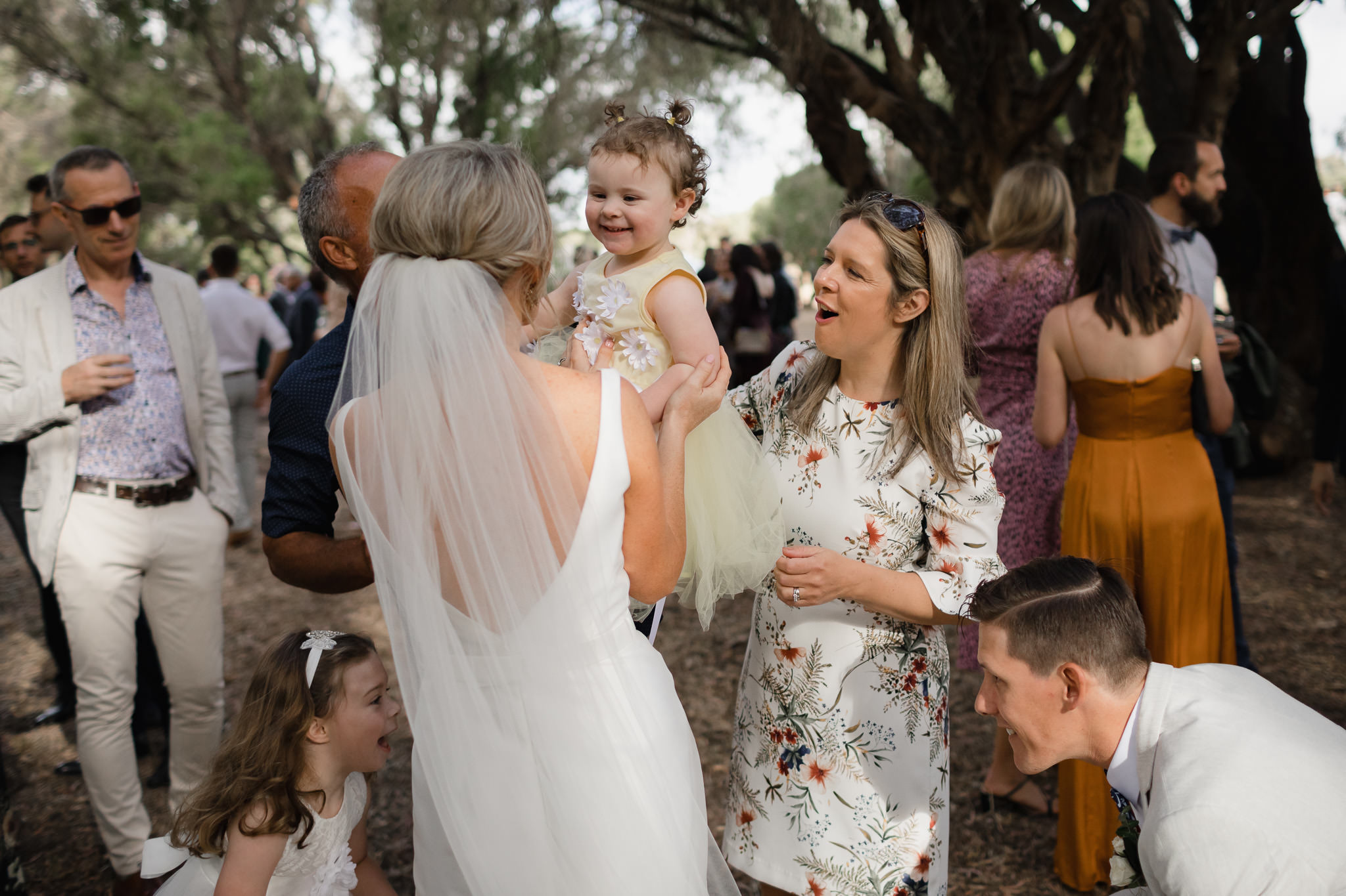 Bride hugging friend's small child at wedding while groom plays peekaboo with flowergirl
