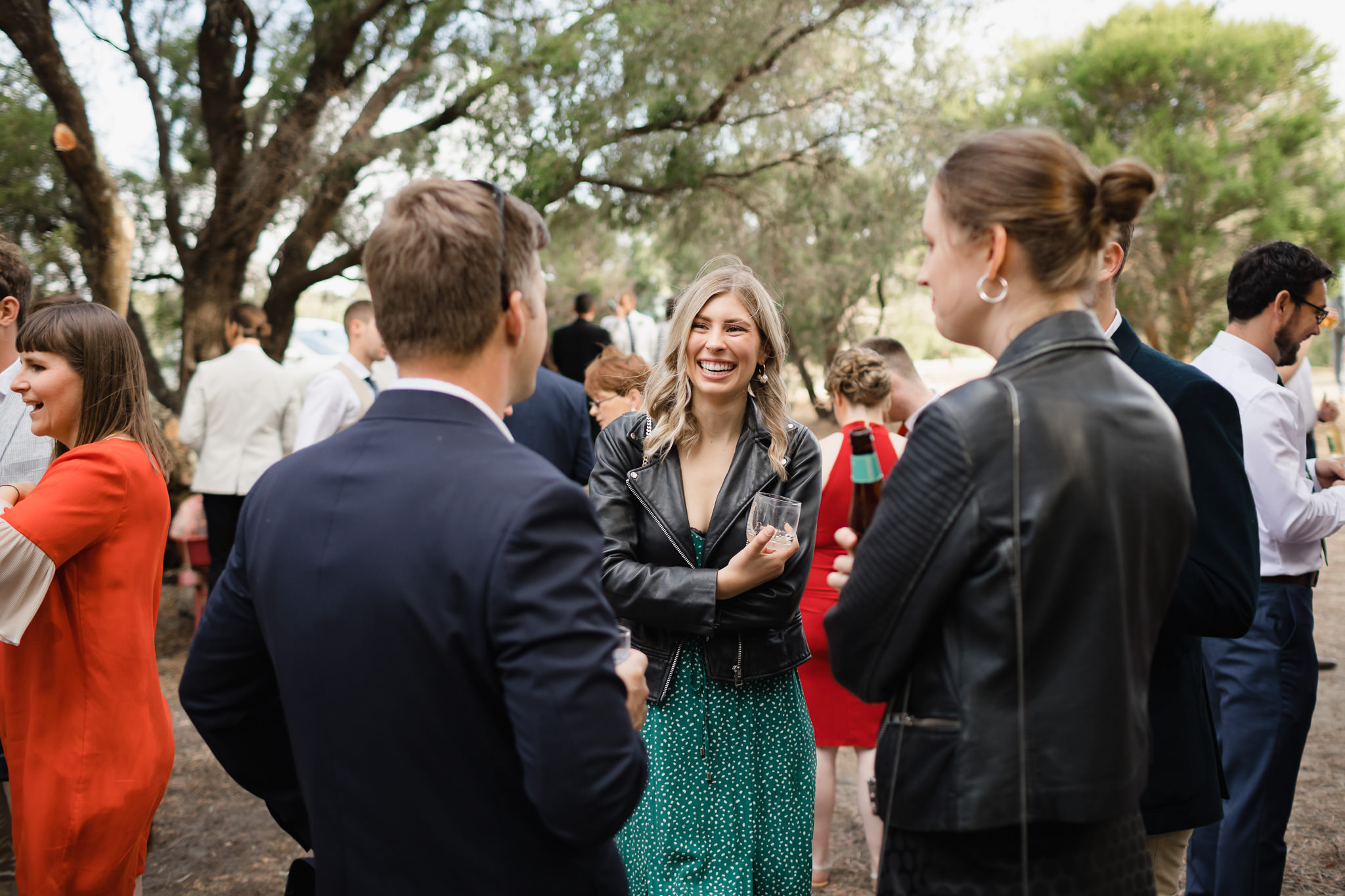 Girl in leather jacket and green dress with white polkadots laughing during wedding celebrations