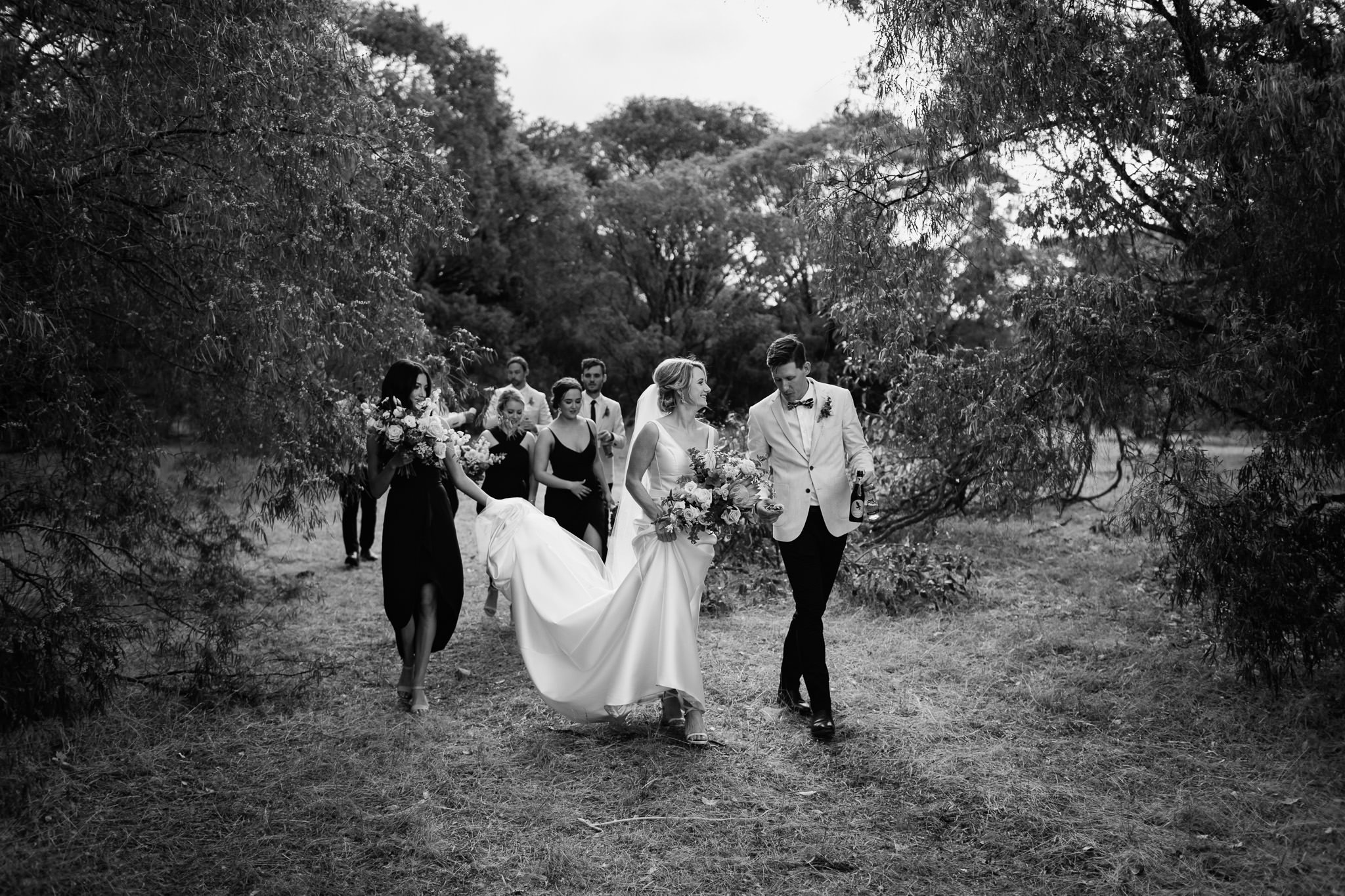 black and white photo of bride, groom and bridal party walking through Australian bush at farm wedding in Yallingup